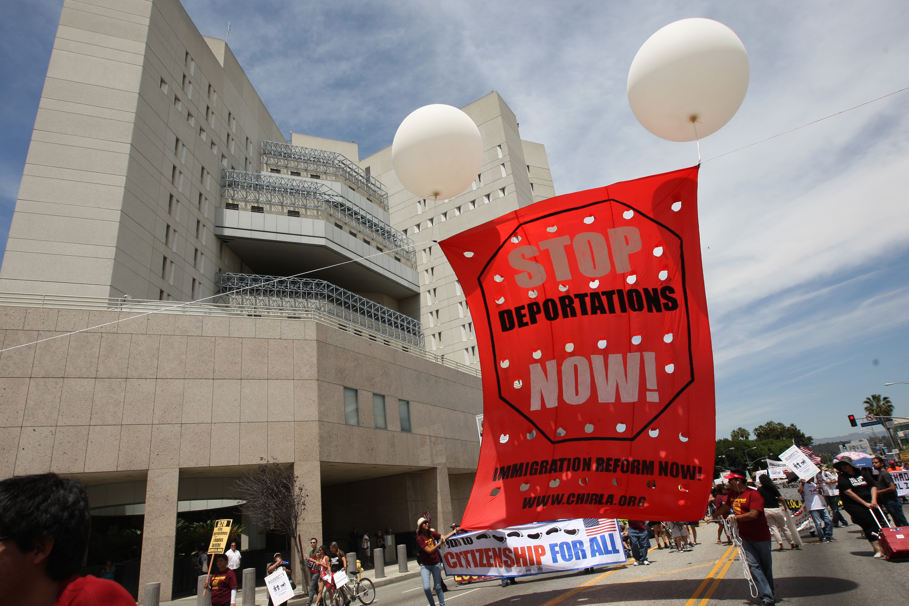 Marchers pass by the Metropolitan Detention Center during one a several May Day immigration-themed events on May 1, 2014 in Los Angeles, California.