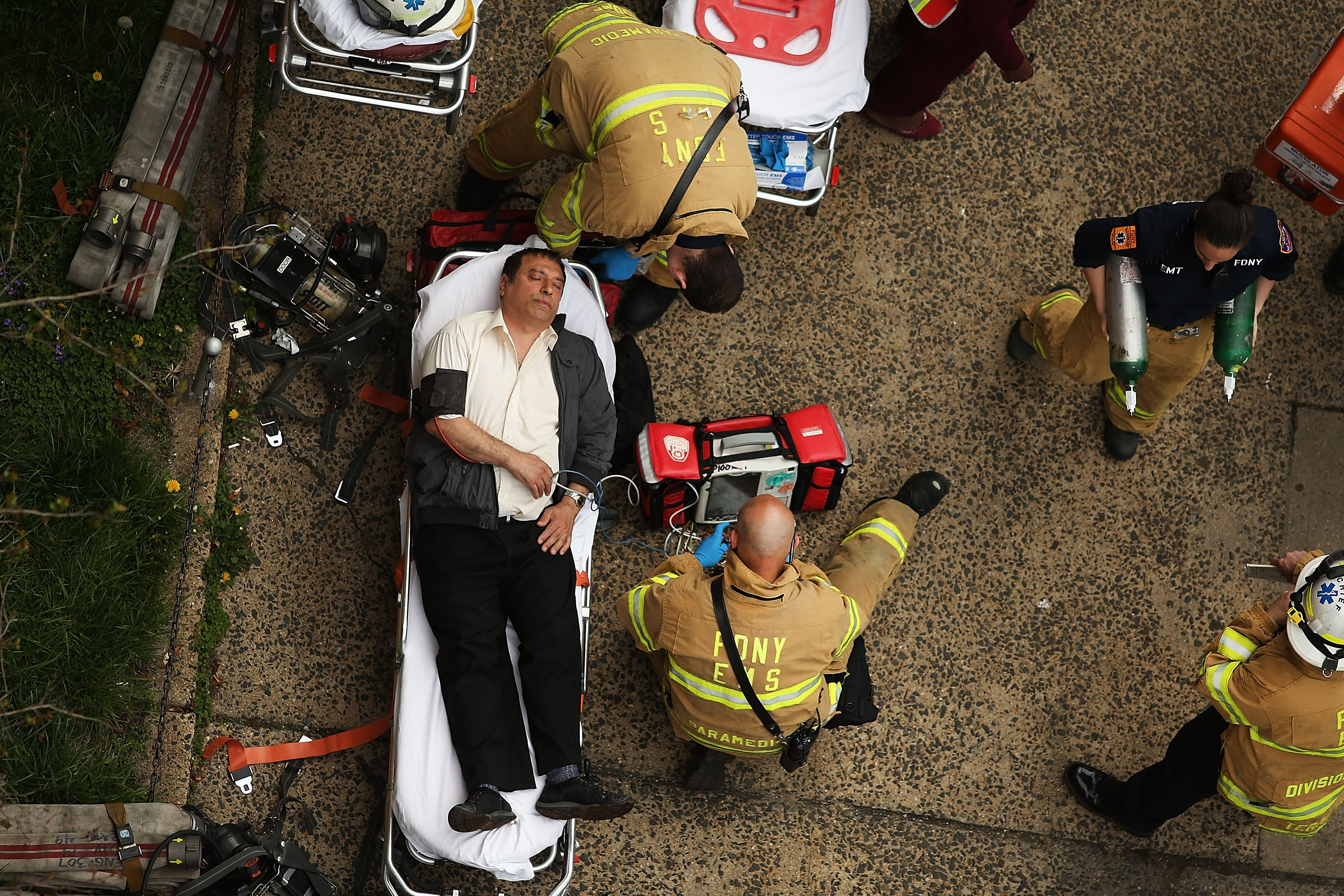 An injured man is aided by New York City firefighters after being evacuated from an emergency staircase following an F train derailment in the Woodside neighborhood of the Queens, N.Y., May 2, 2014.