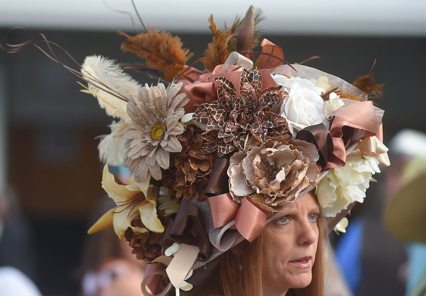 Tami Purcell of Knoxville, Tenn. looks on wearing a festive, natural toned Derby hat.