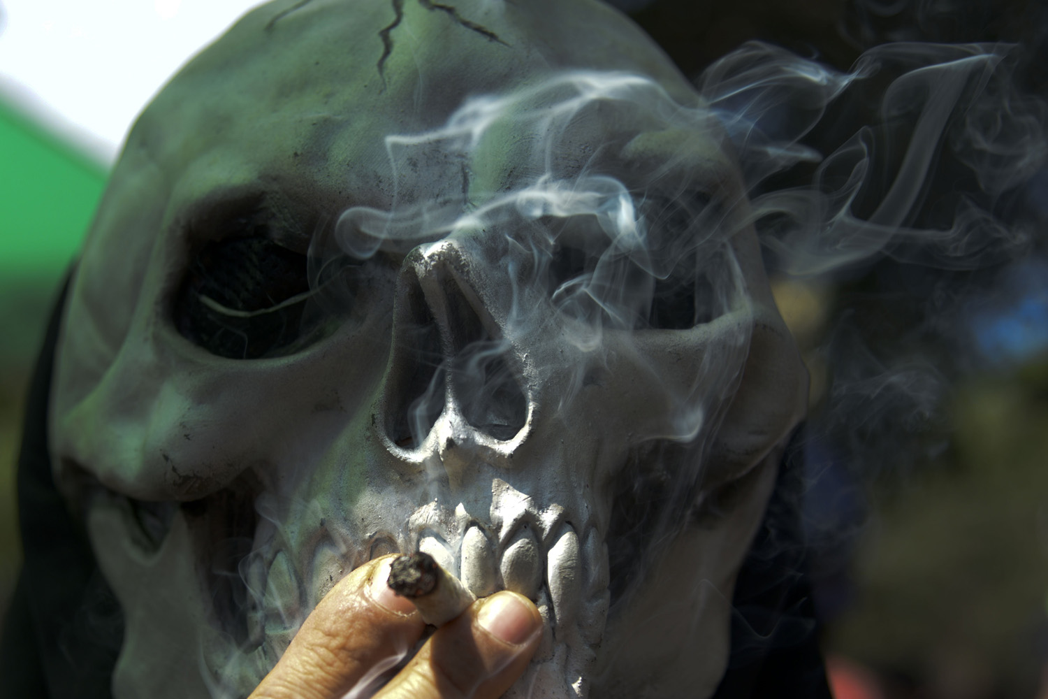 May 3, 2014. A masked person smokes marijuana during the World Day for the Legalization of Marijuana in Medellin, Antioquia department, Colombia.