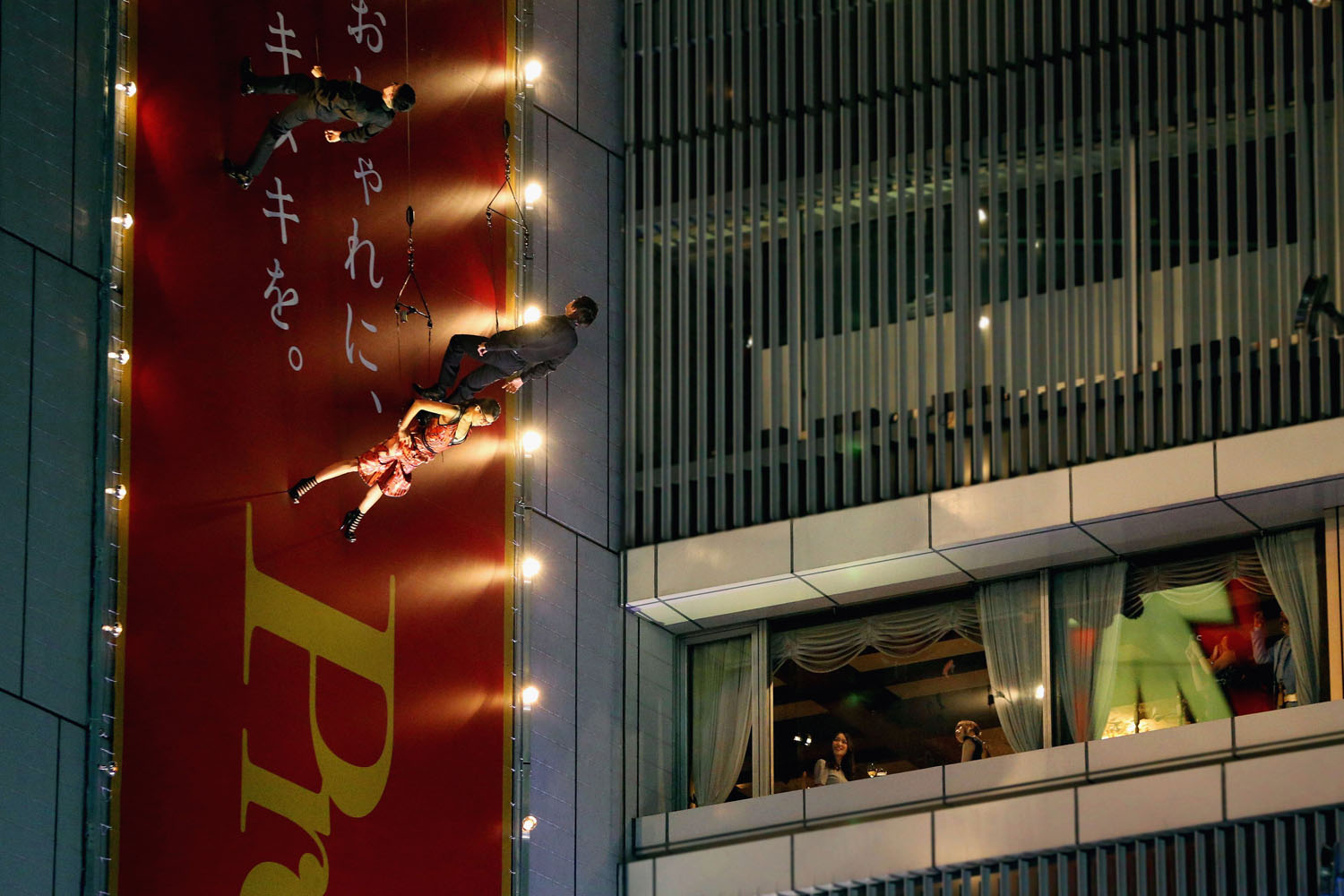 May 7, 2014. Models walk on the runway set on the wall of the Sony Building during the 'Sky Fashion Show' while people watch from the building at Tokyo's shopping district of Ginza on  in Tokyo, Japan.