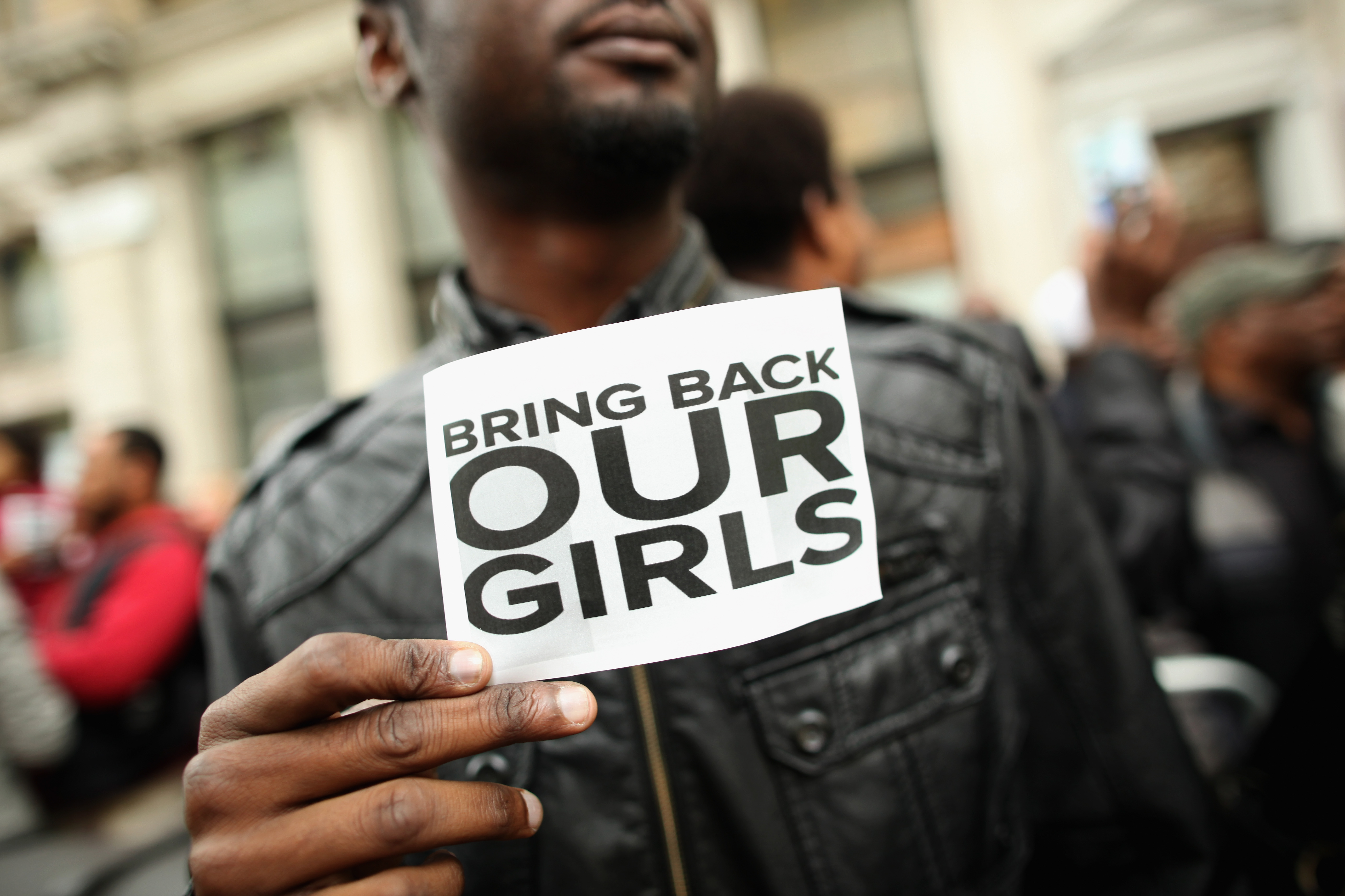 A man holds a sign that reads  Bring Back Our Girls  during a protest outside Nigeria House in London on May 9, 2014
