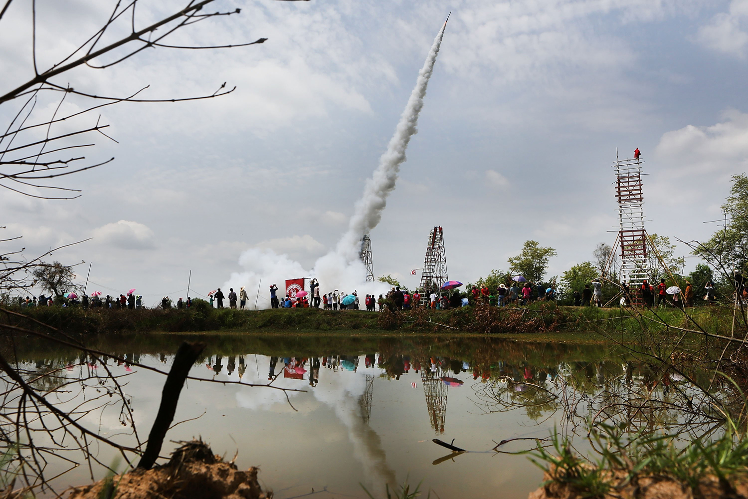 May 11, 2014. Yasothon resident look on as huge, handmade rockets are launched into the air during the Bun Bang Fai festival in Yasothon, Thailand.