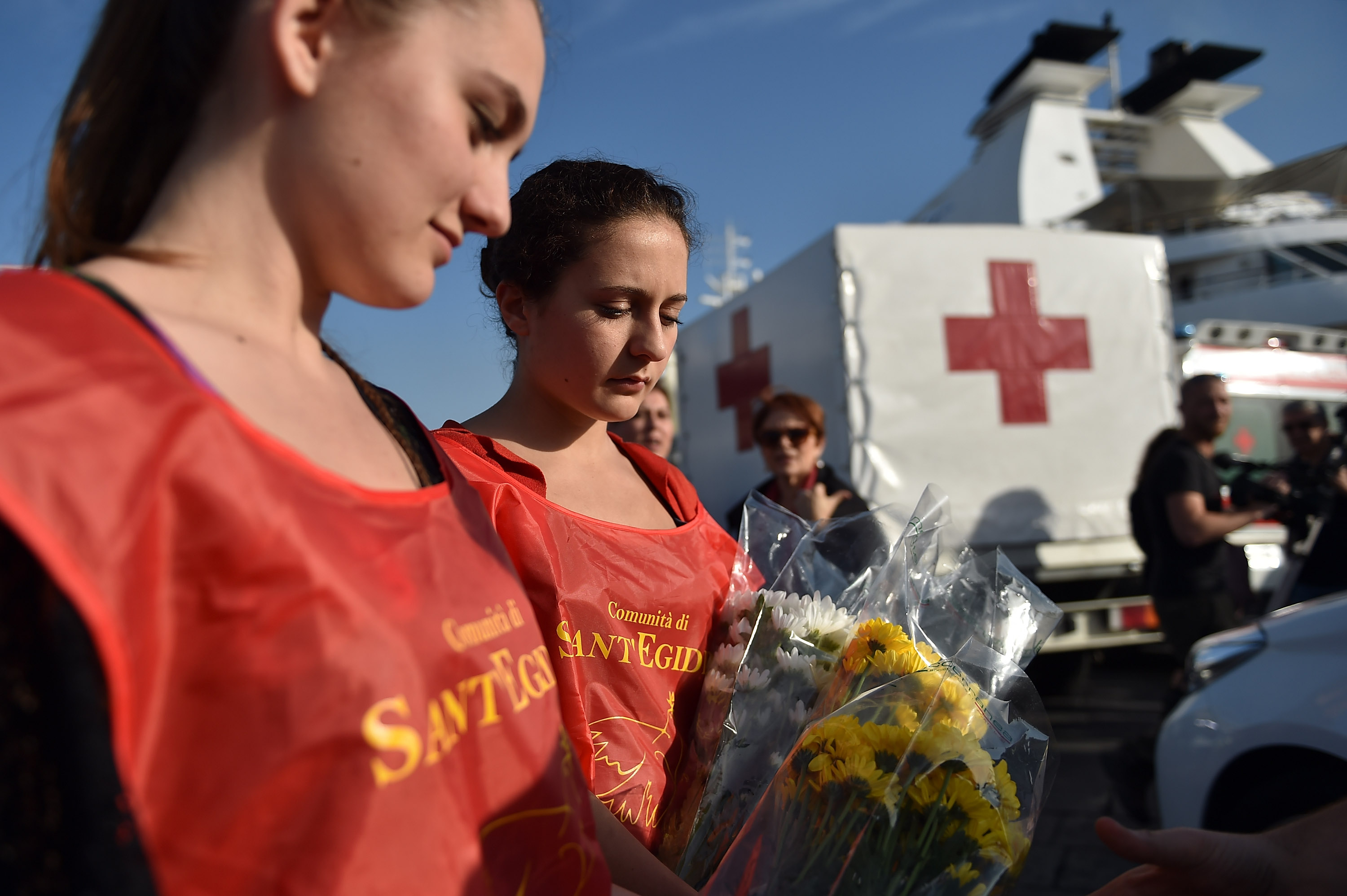 Sant'Egidio Community volunteers hold flowers while waiting arrival of Italian Navy Ship Grecale arriving at the Port of Catania, carrying 206 migrants and 17 bodies of the victims of a shipwrecked boat between Sicily and the north of Africa on May 13, 2014