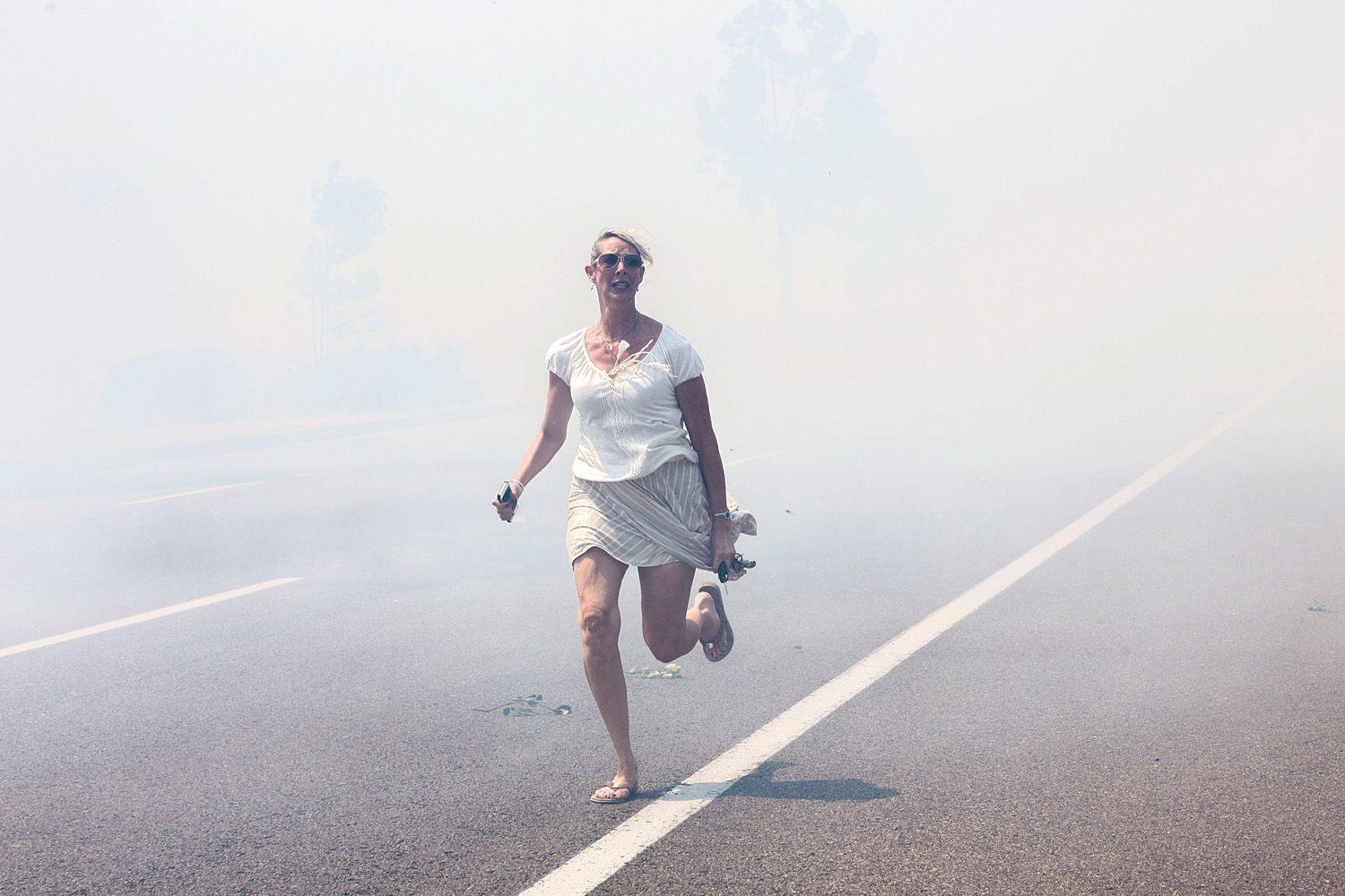 May 14, 2014. A woman flees the Poinsettia Fire as it crosses El Camino Real in Carlsbad, California.