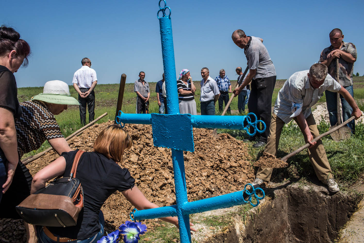 May 16, 2014. Mourners fill in the grave of Elena Ott, 42, in Starovarvarovka, Ukraine. Ott was killed two days prior when the car she was riding in was fired on by forces her family believes to be the Ukrainian military.