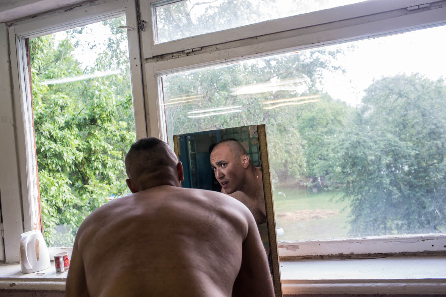 May 19, 2014. A new recruit checks his haircut at a training camp for the Donbass Battalion, a pro-Ukrainian militia in Dnipropetrovsk Region, Ukraine.