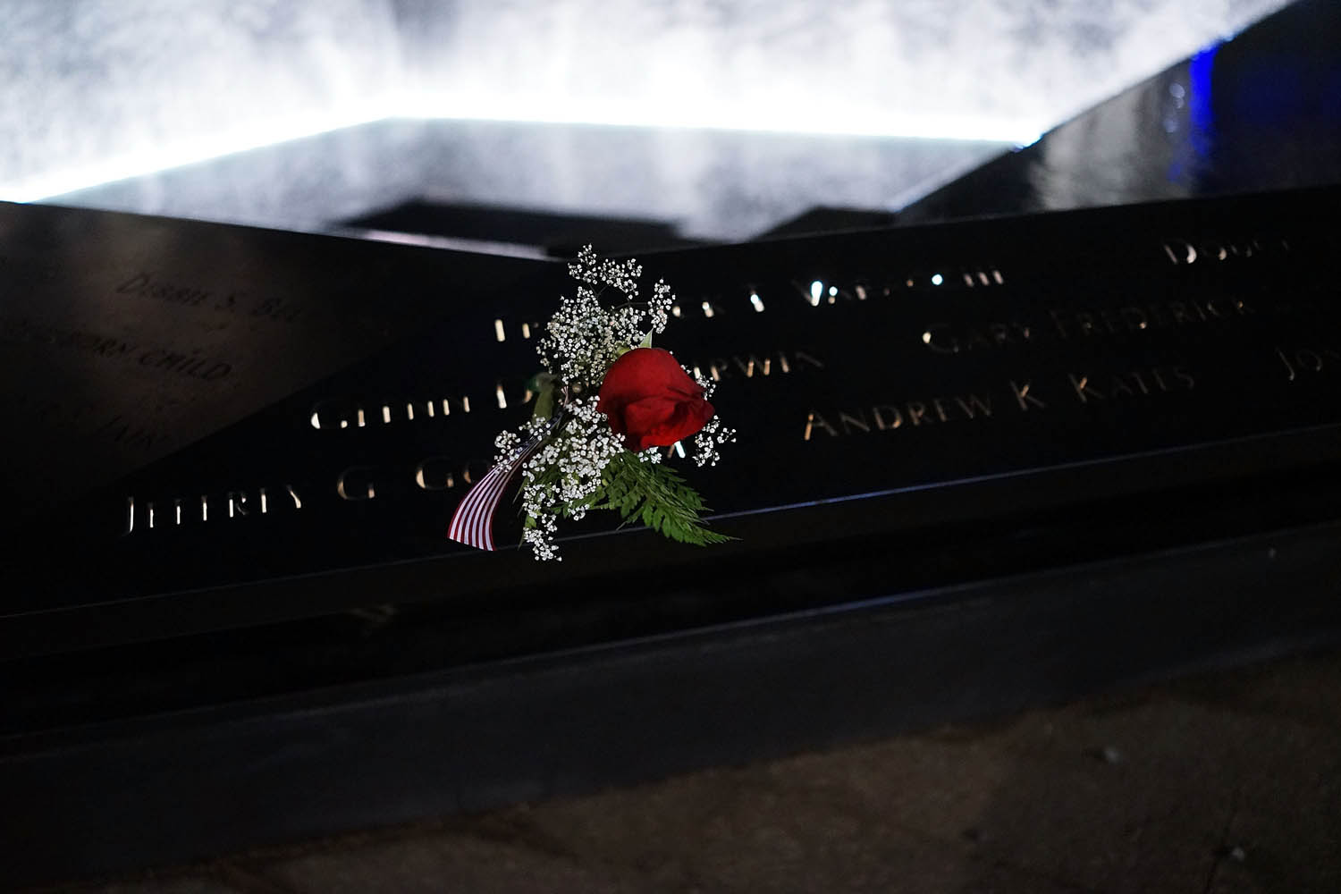 May 19, 2014. An American flag and a rose are viewed in a name along the reflecting pool at the ground zero memorial site after authorities recently took down gates and opened the plaza to the public in New York City.