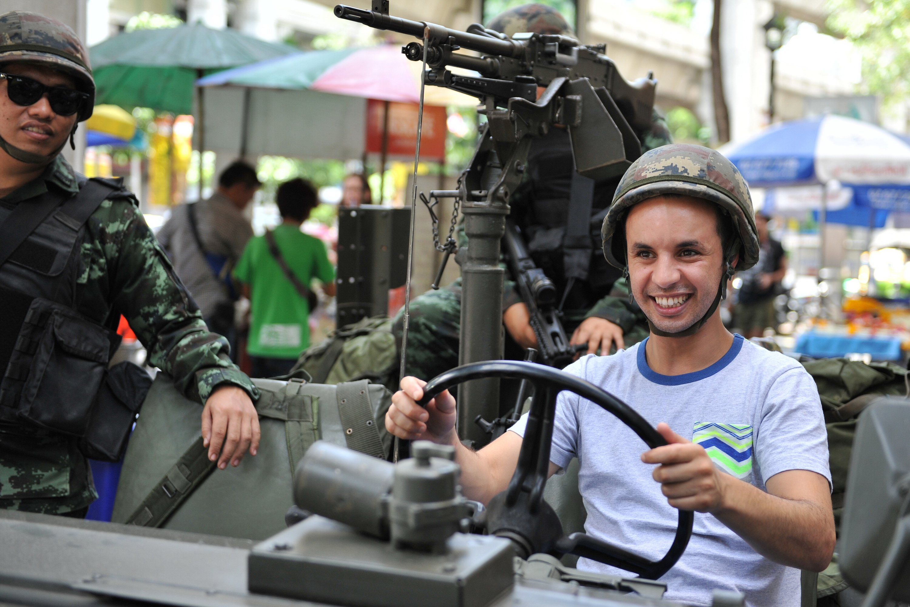 A foreign tourist sits in a Thai army vehicle as soldiers deploy on a downtown street after martial law was declared on May 20, 2014 in Bangkok.