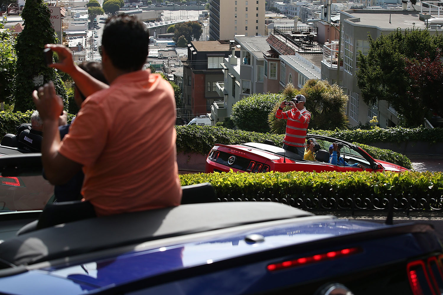 Tourists take pictures while driving down Lombard Street in San Francisco, on May 20, 2014.