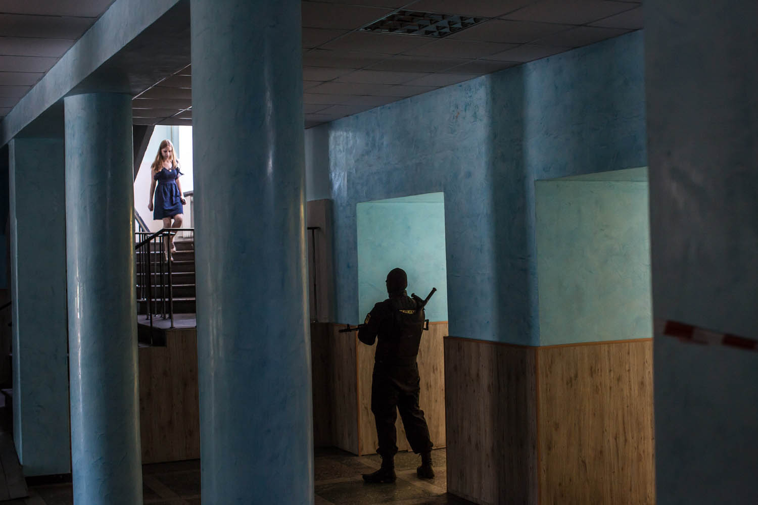 May 21, 2014. A member of the Donbass Battalion, a pro-Ukraine militia, secures the lobby during a meeting with the local mayor to ensure the integrity of the upcoming presidential election in Dobropillya, Ukraine.