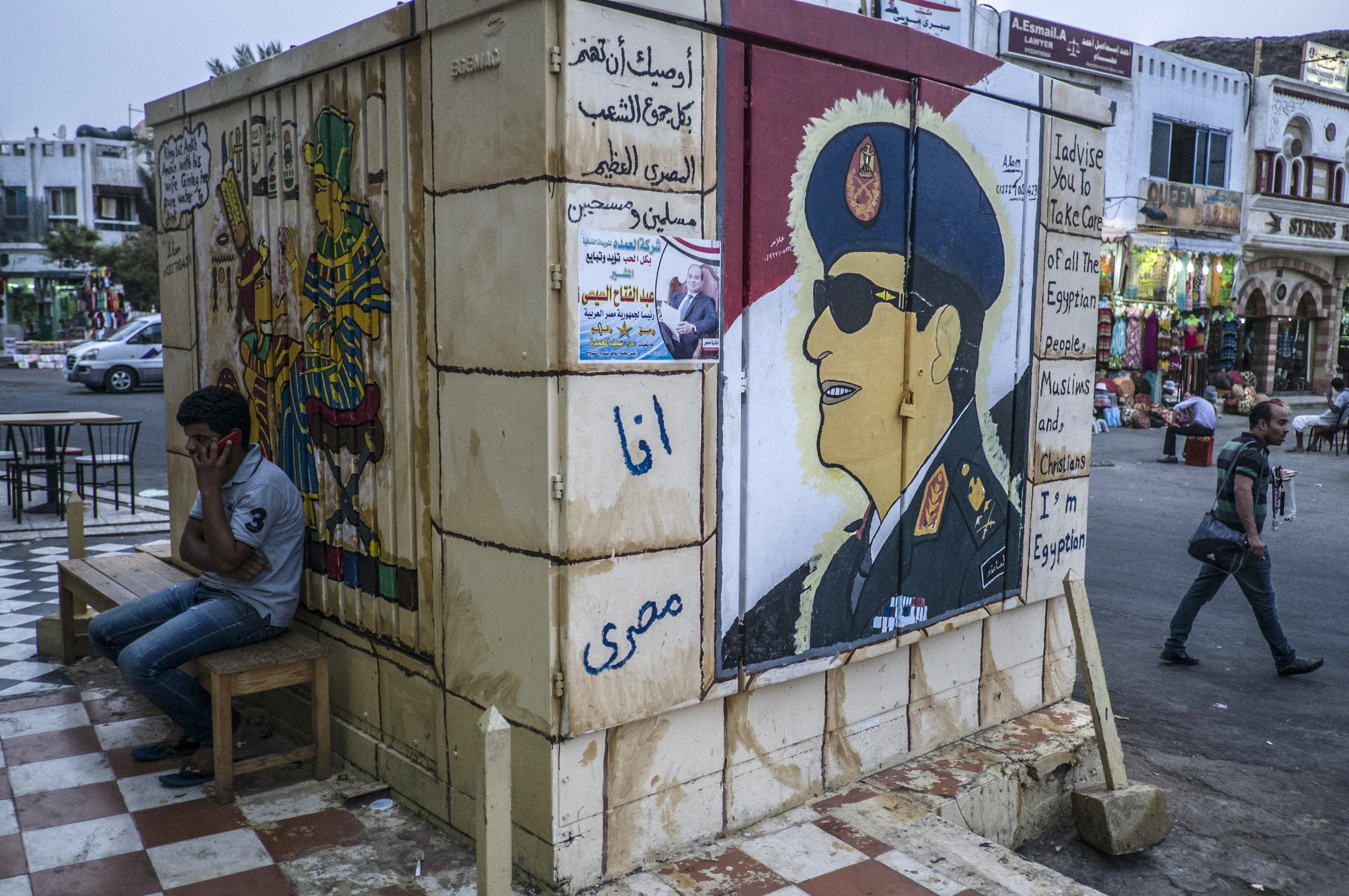 An Egyptian man sits next to graffiti of Egypt's ex-army chief and leading presidential candidate Abdel Fattah al-Sisi  in Egypt's Red Sea resort of Sharm el-Sheikh on May 21, 2014.