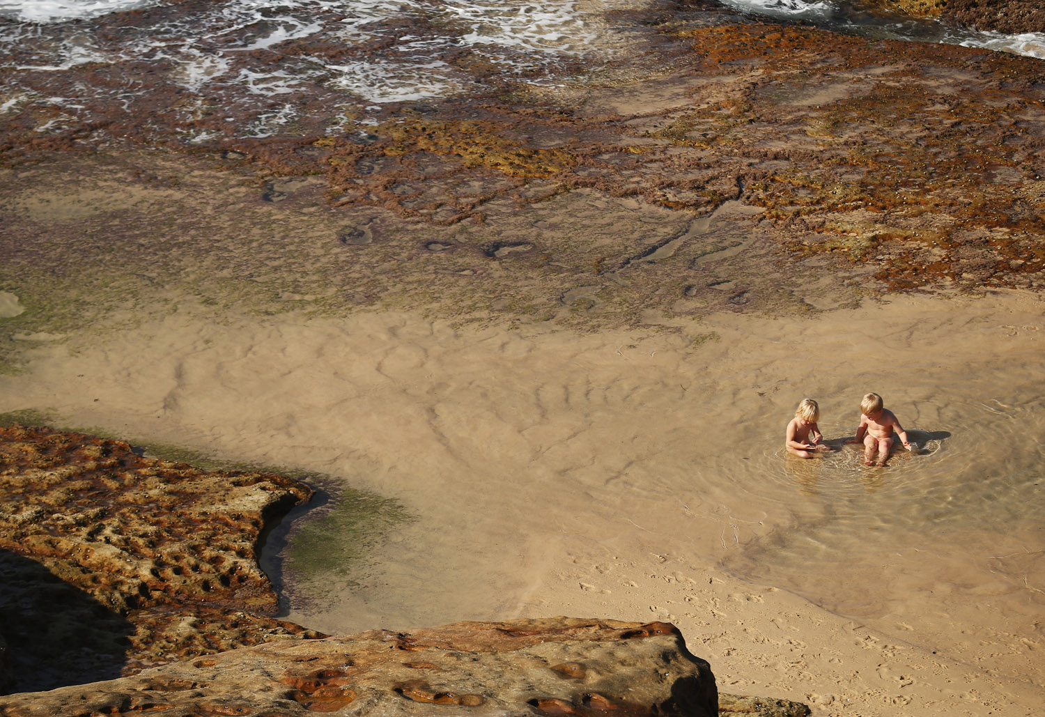 Children play in a pond in Sydney which is experiencing it's hottest May on record, on May 23, 2014.