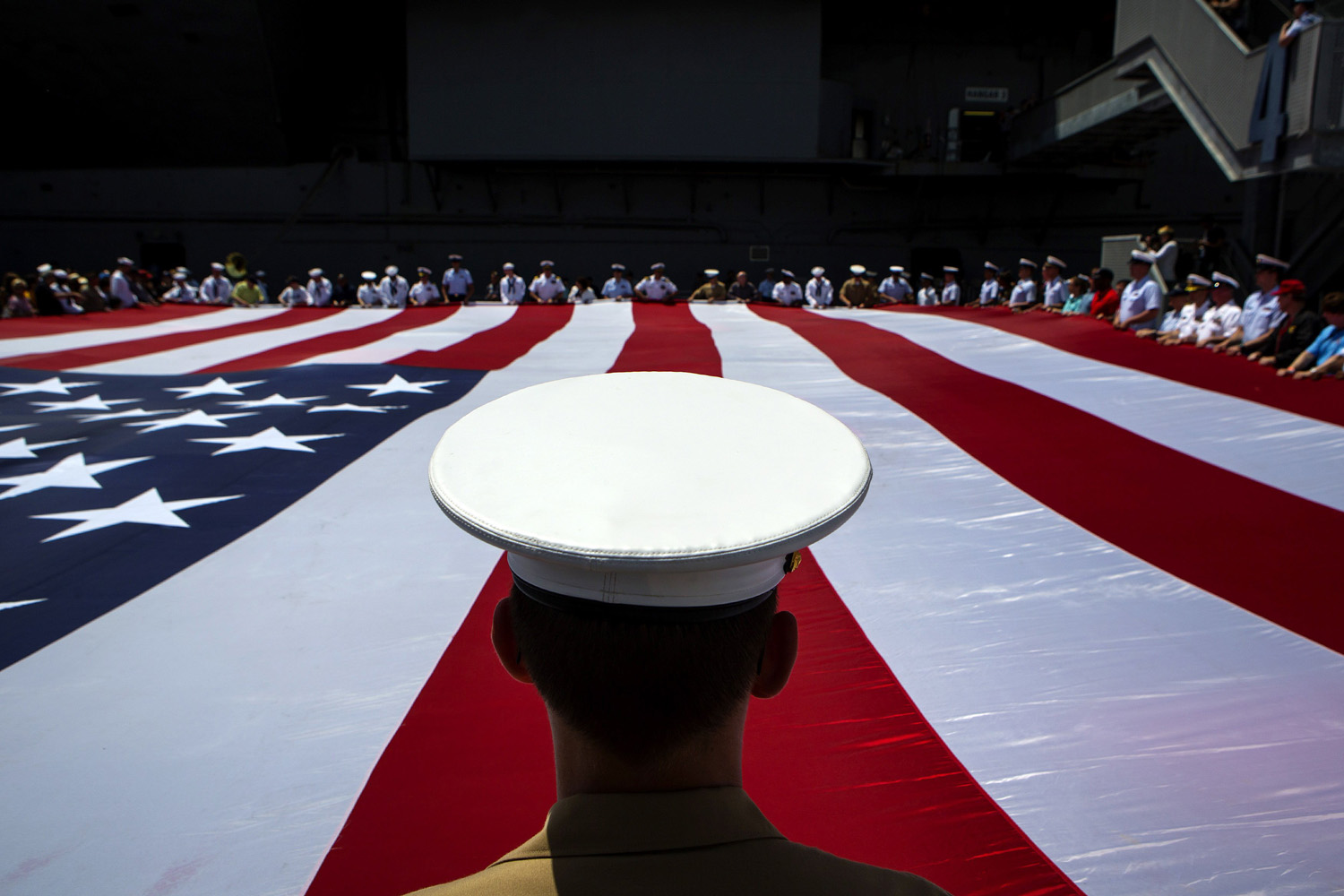 May 26, 2014. Members of the military unfurl an American flag during a wreath laying ceremony at the Intrepid Sea, Air and Space Museum in New York City.