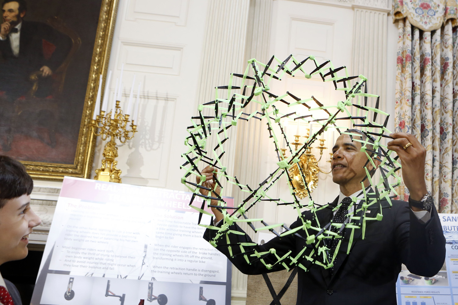 U.S. President Barack Obama looks at the project of Peyton Roberston (left) from Ft. Lauderdale, Fla., winner of the Discovery 3M Young Scientist, for his  Sandless sand bags  project at the 2014 White House Science Fair in Washington, D.C., May 27, 2014.