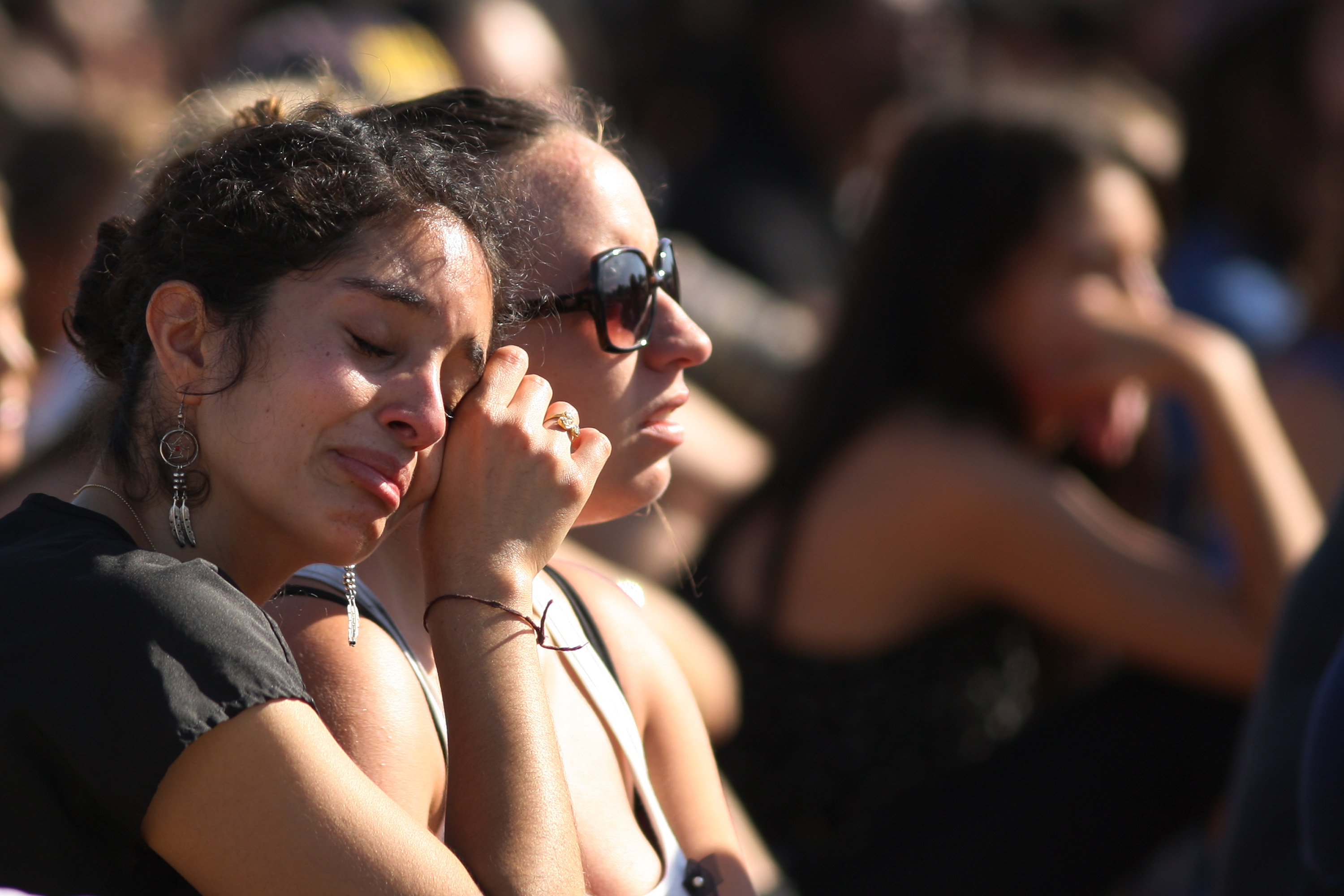 Students mourn at a public memorial service on the Day of Mourning and Reflection for the victims of a killing spree at University of California, Santa Barbara on May 27, 2014 in Isla Vista, California.