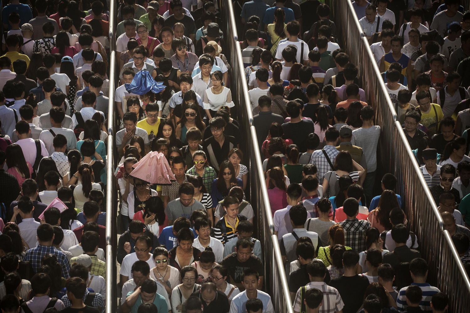 May 29, 2014. Chinese commuters line-up at a security check to enter a subway station in Beijing, China.
