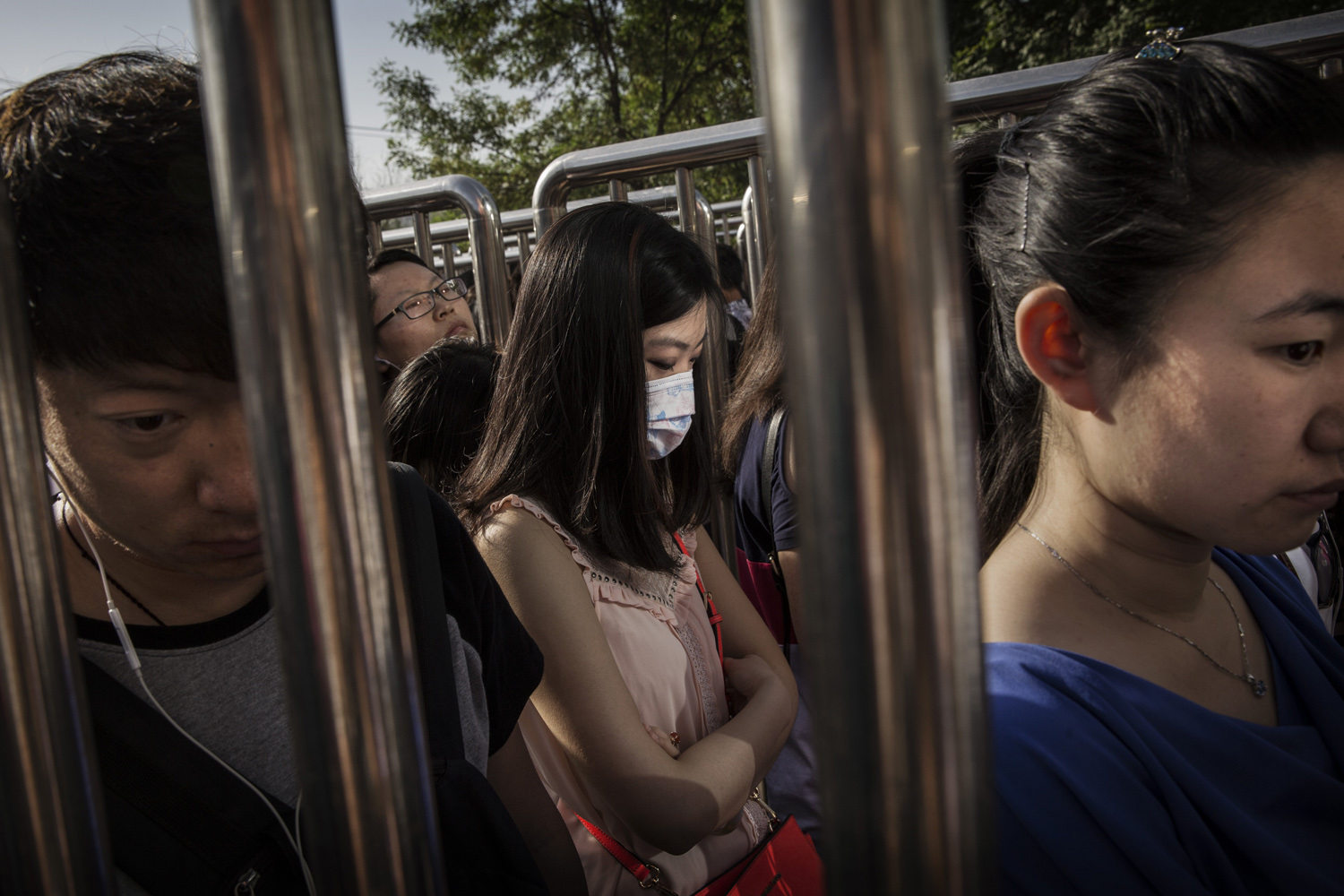 May 29, 2014. Chinese commuters line-up for a security check at a subway station in Beijing, China.