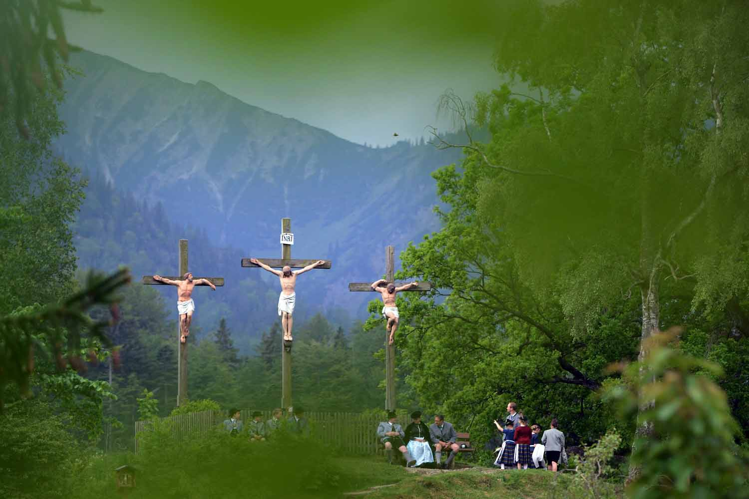 May 29, 2014.  Pilgrims in traditional Bavarian folk costumes stand beneath three crosses on the Kalvarienberg-mountain and follow an outdoor mass to celebrate Ascension (in German called Christi Himmelfahrt) at the open-air altar at Birkenstein on near Fischbachau, Germany.