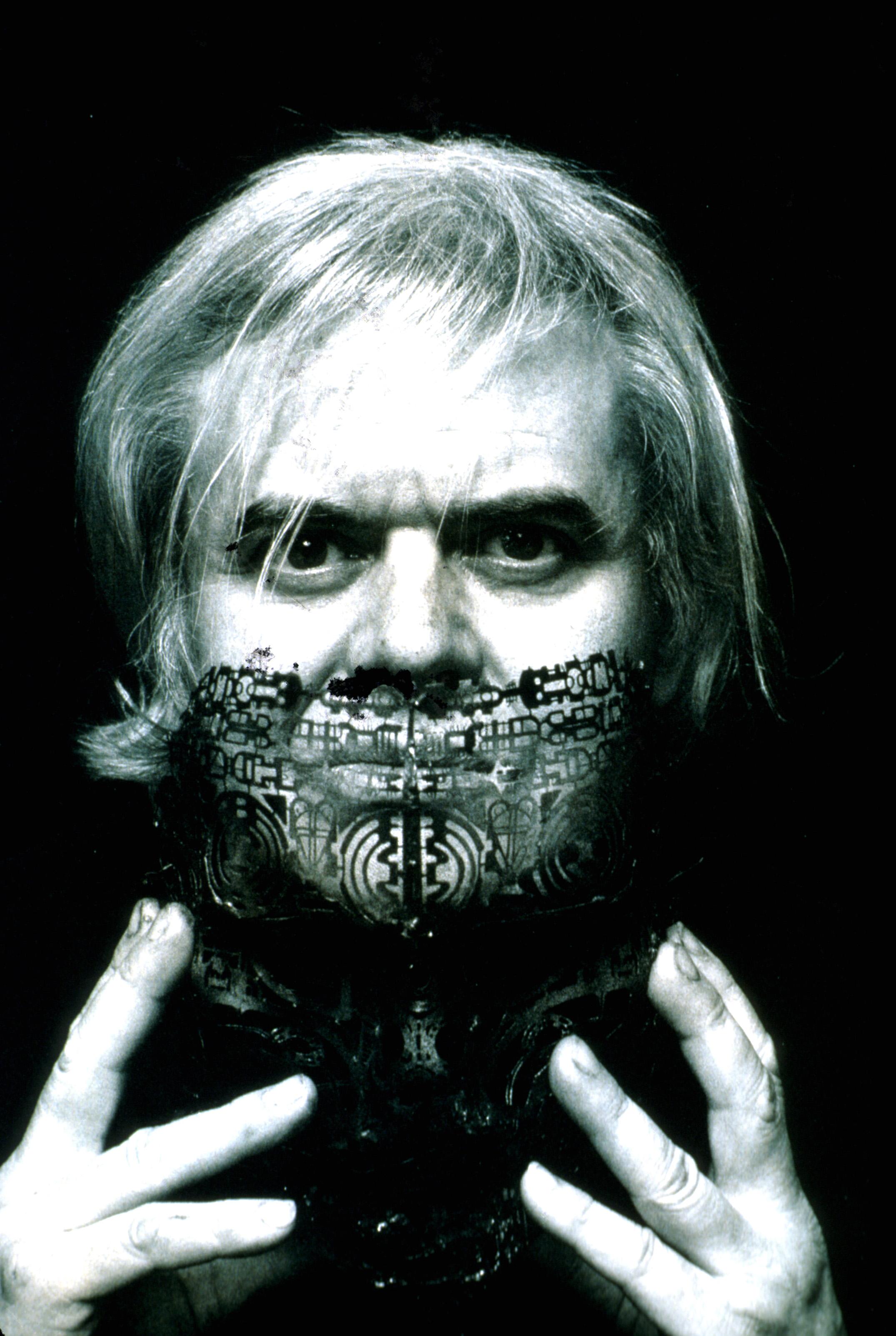 Visual artist H. R. Giger taking off face mask.
