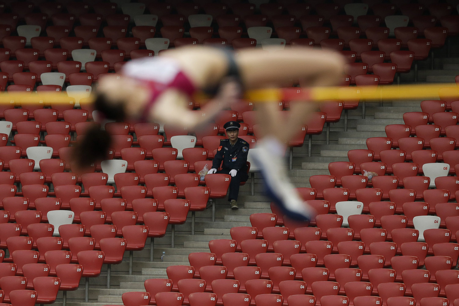 May 21, 2014. A security guard watches as Russia's Elena Slesarenko, front, makes an attempt at the women's high jump during the 2014 IAAF World Challenge Beijing held at China's National Stadium in Beijing.