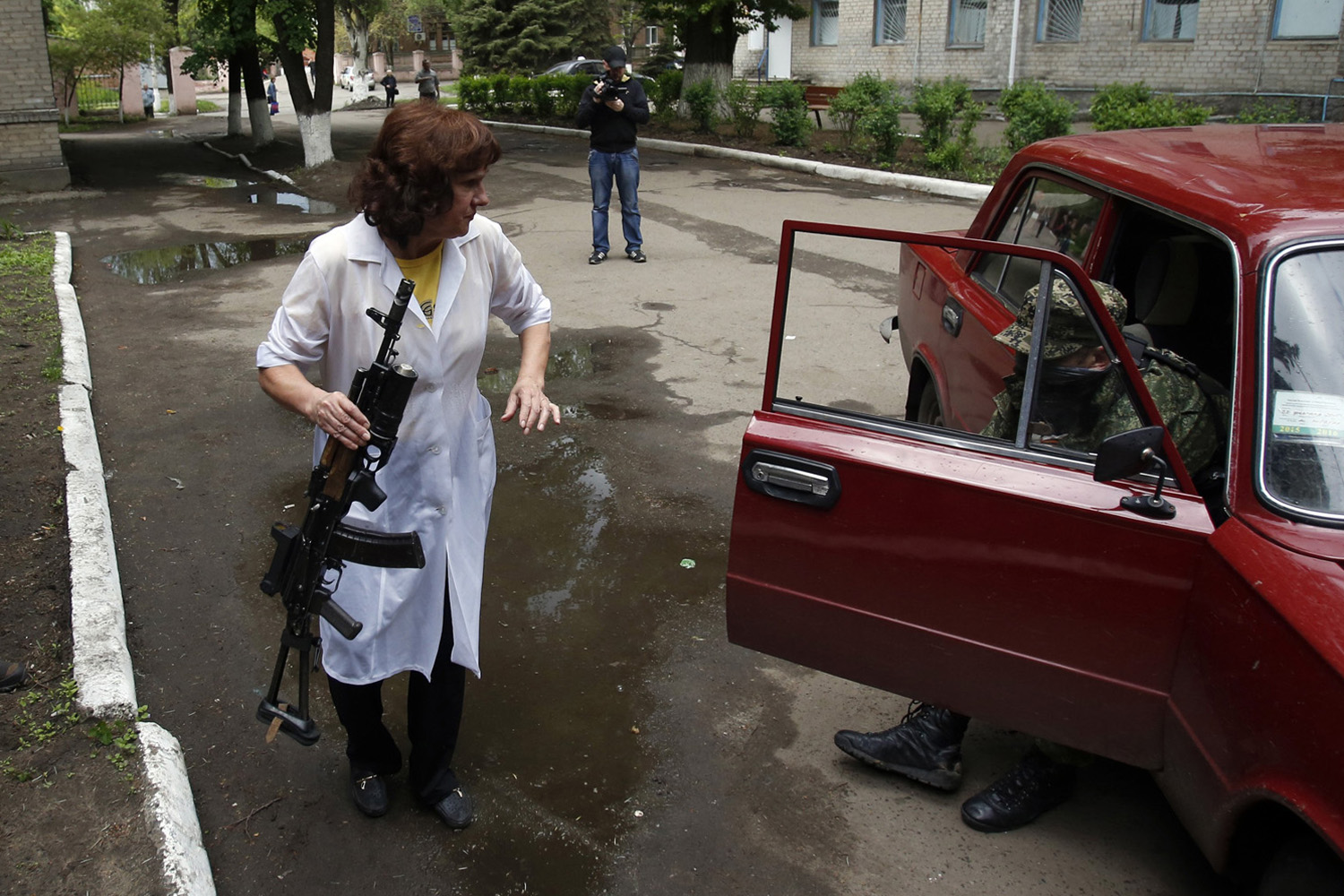 A nurse holds a gun as she helps a wounded Pro-Russian gunmen to get out of the car in front of local hospital in Slovyansk, eastern Ukraine, on May 5, 2014.