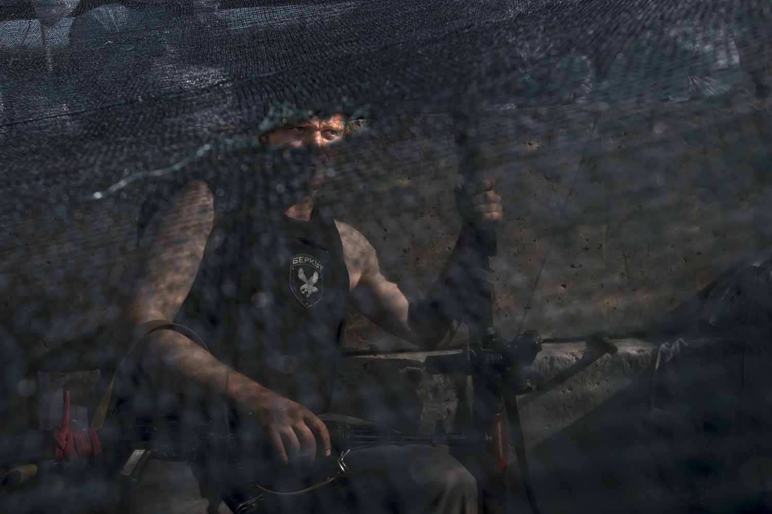 May 26, 2014. A pro-Russian armed militant wearing a shirt bearing an emblem of a former Ukrainian special force police unit sits behind a camouflage net as he guards a checkpoint blocking the major highway which links the Russian city of Rostov-on-Don, and Kharkiv, outside Slovyansk, Ukraine.