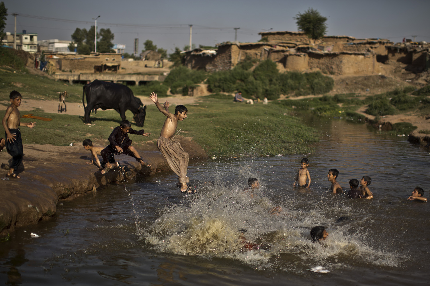 An Afghan refugee boy jumps into the water while he and others swim in a polluted stream to cool off as the temperature rises, on the outskirts of Islamabad, Pakistan on May 28, 2014.