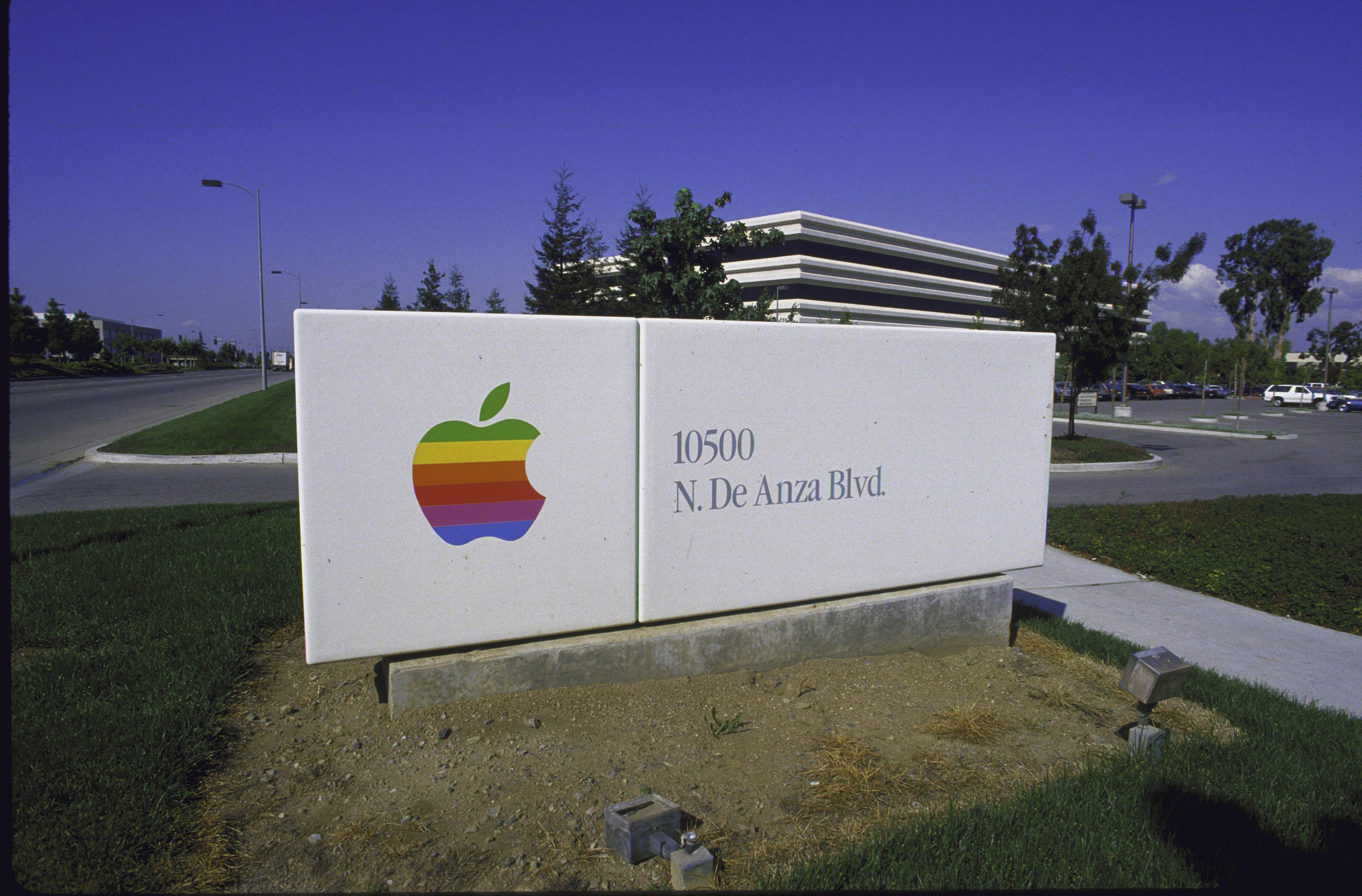 Sign with Apple logo in front of Apple Computer building.