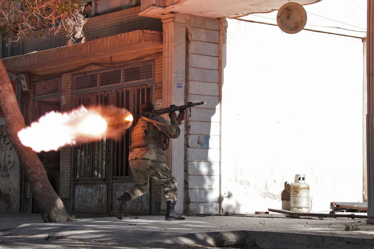 May 23, 2014. An Afghanistan National Army (ANA) soldier fires his weapon at the site of a clash between insurgents and security forces at  the Indian Consulate in Herat, Afghanistan.