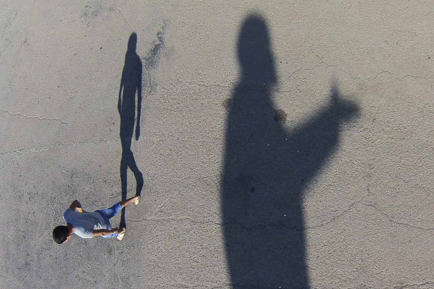 May 27, 2014. A man walks past a shadow of statue of Soviet Union founder Vladimir Lenin at the Russian leased Baikonur cosmodrome, in Kazakhstan.