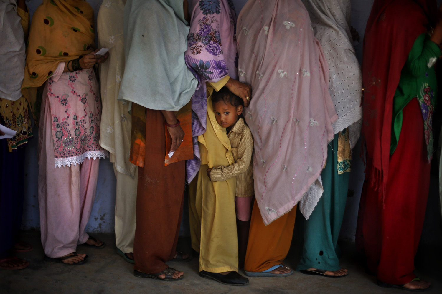 May 15, 2014. A young boy clings to the leg of his mother who stands in a queue to cast her vote during a re-polling of Indian parliamentary elections in Rehna village, in the northern Indian state of Haryana.