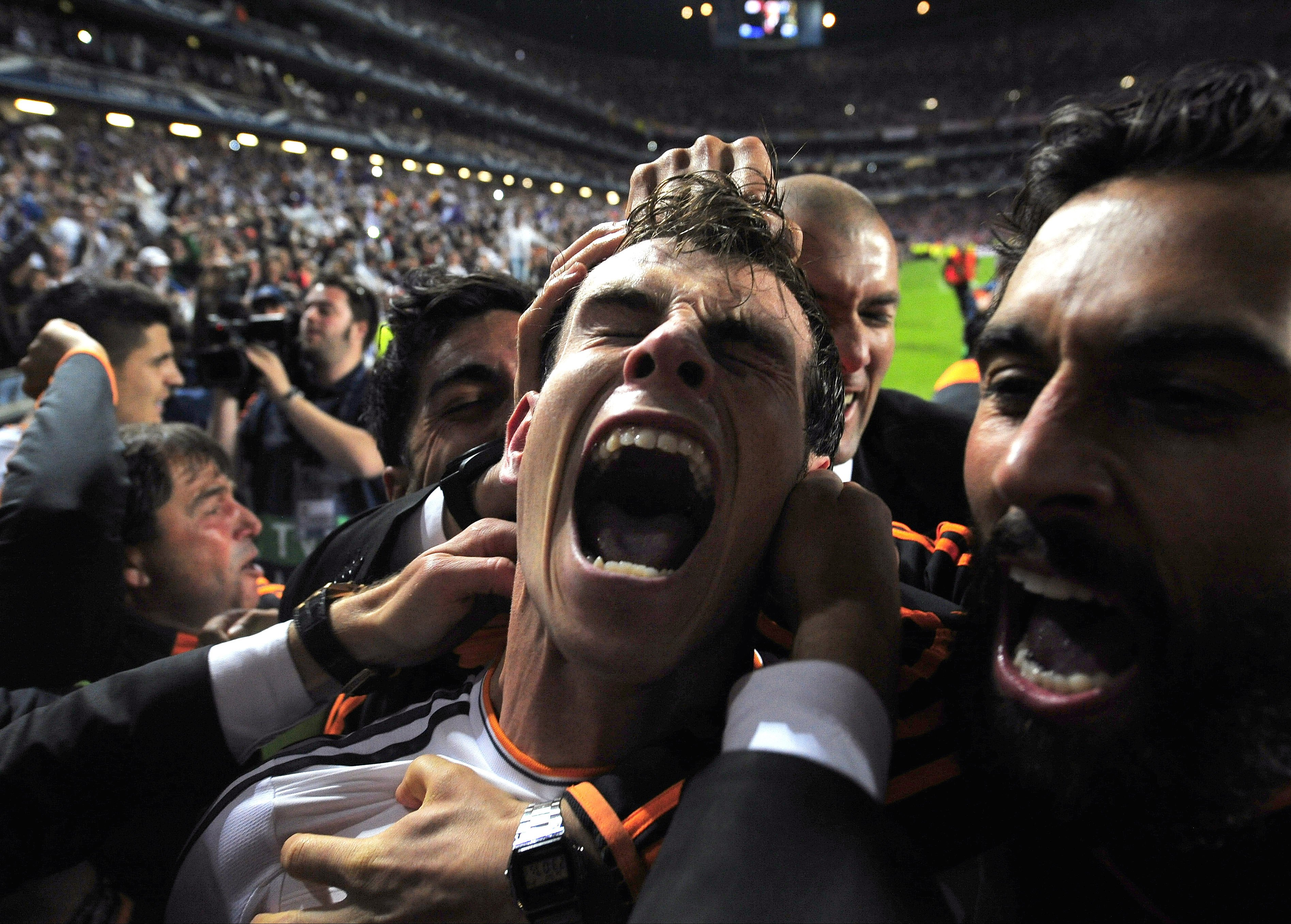 Real Madrid's Gareth Bale celebrates with teammates after scoring his second goal in the Champions League final soccer match against Atletico Madrid at the Luz Stadium in Lisbon on May 24, 2014.