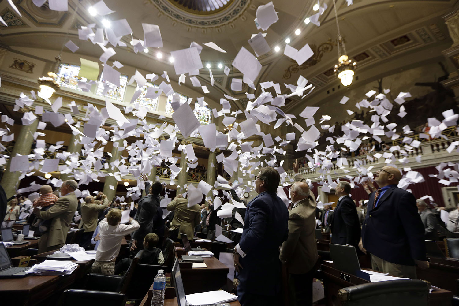 Members of the Missouri House of Representatives throw papers in the air in celebration of the end of the legislative session in Jefferson City, Mo., on May 16, 2014.
