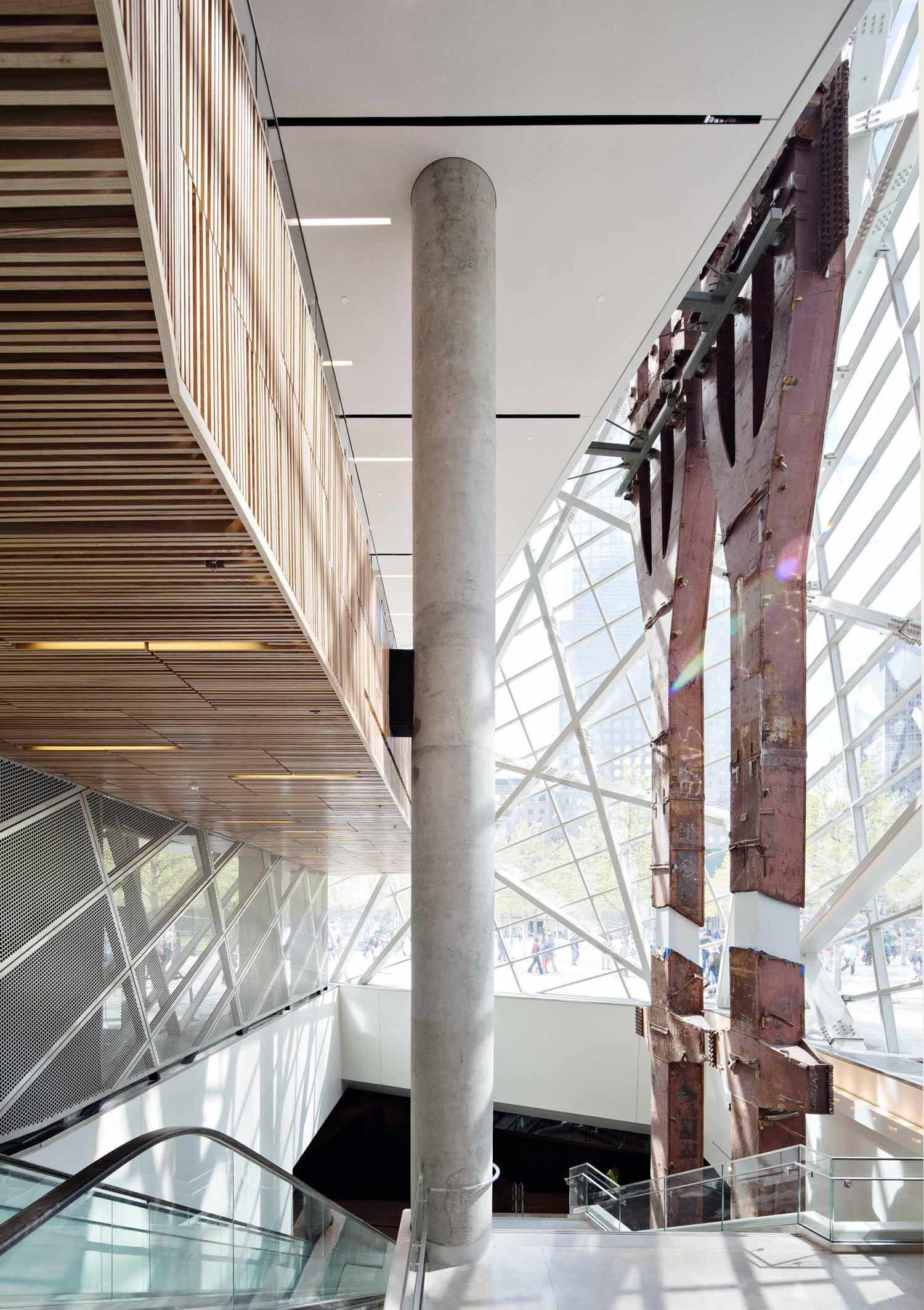"Two 80-ft. (24 m) ""tridents"" from the World Trade Center's facade rise through the glass-enclosed atrium of the museum's entry pavilion, with its crisscrossing steel truss work. The stairway leads down to the mostly under­­ground museum"