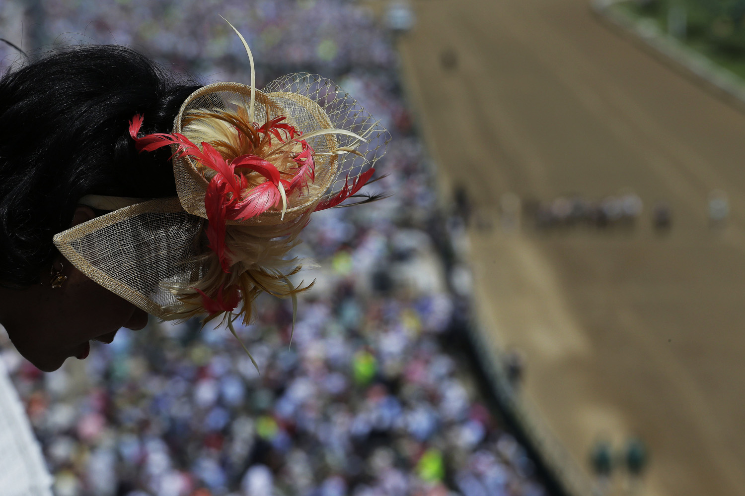 May 3, 2014. A woman looks out over a balcony before the 140th running of the Kentucky Derby horse race at Churchill Downs in Louisville, Ky.