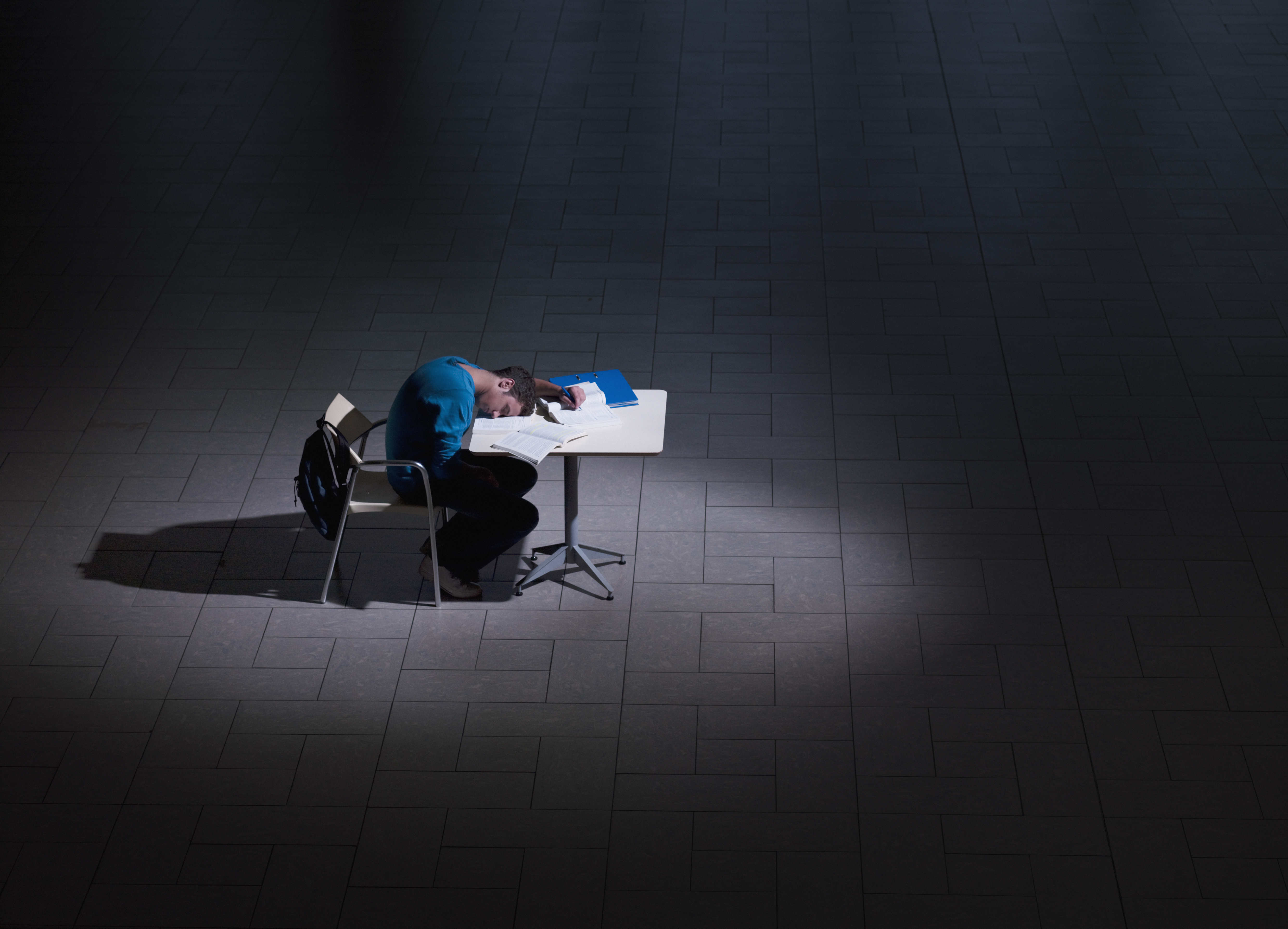 Male student sleeping on desk in darkness