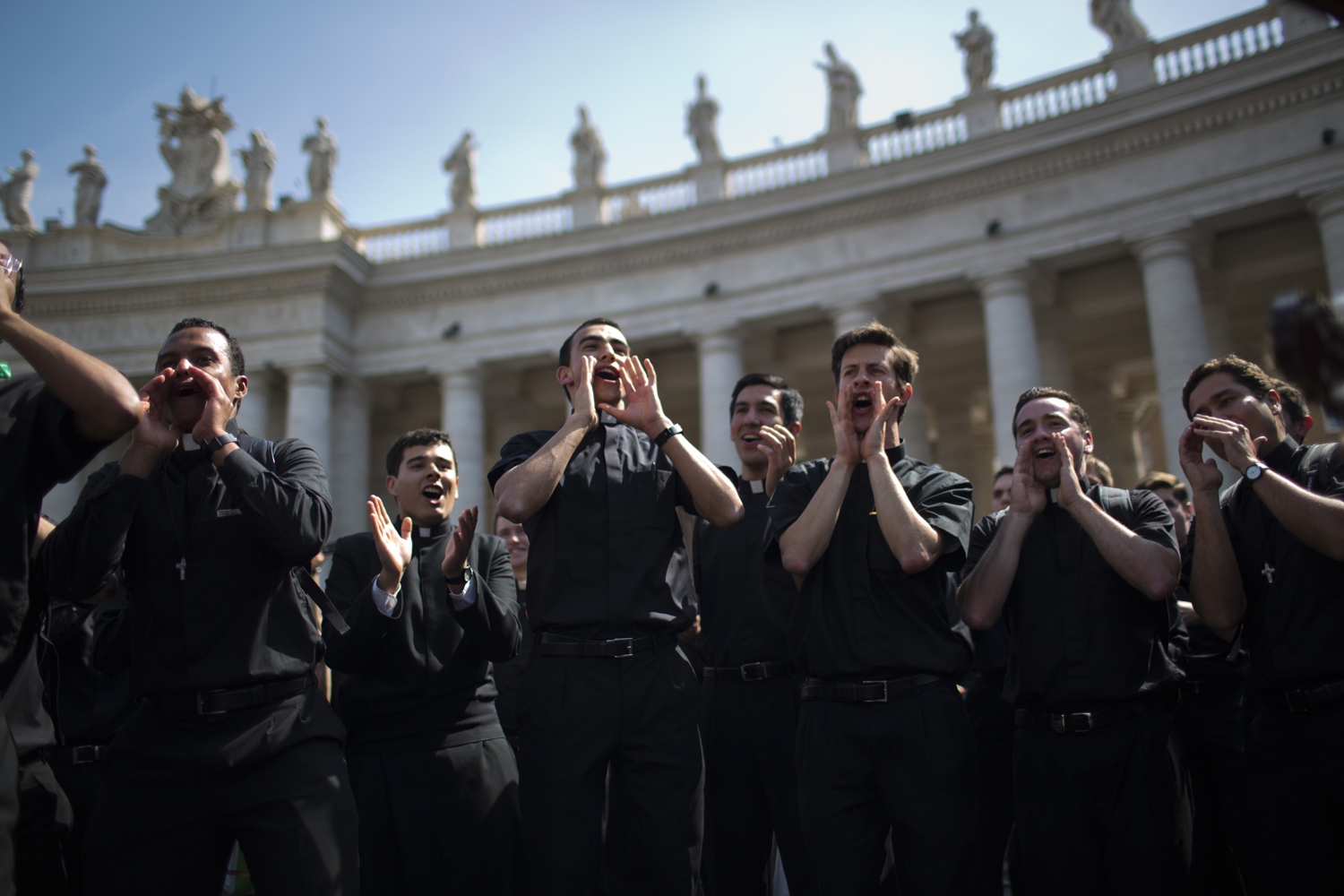 Priests sing and dance in St. Peter's Square at the Vatican, on Saturday, April 26, 2014. Pilgrims and faithful are gathering in Rome to attend Sunday's ceremony at the Vatican where Pope Francis will elevate in a solemn ceremony John XXIII and John Paul II to sainthood.