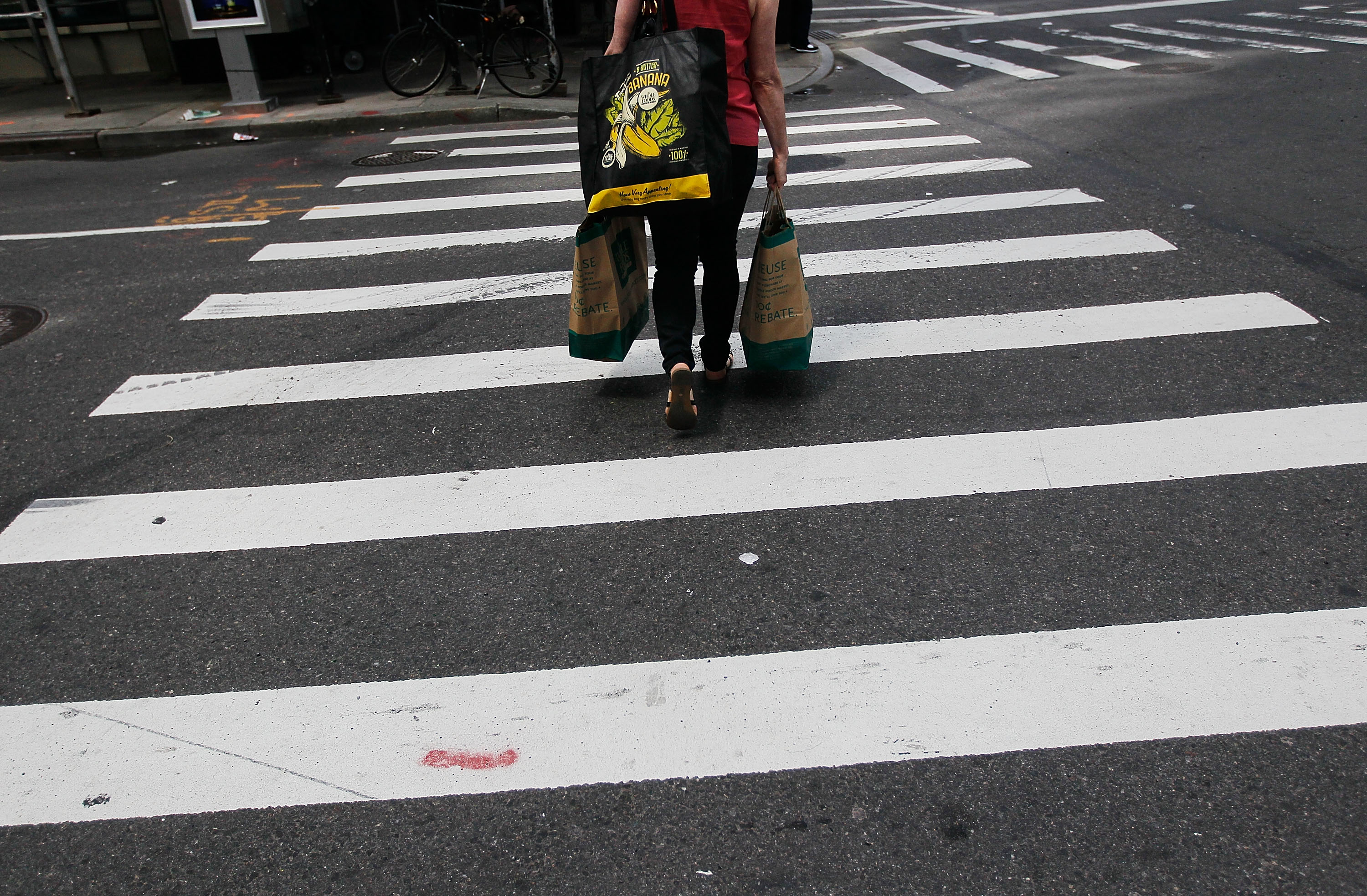 A woman with shopping bags traverses a crosswalk near Columbus Circle April 30, 2010 in New York, New York.