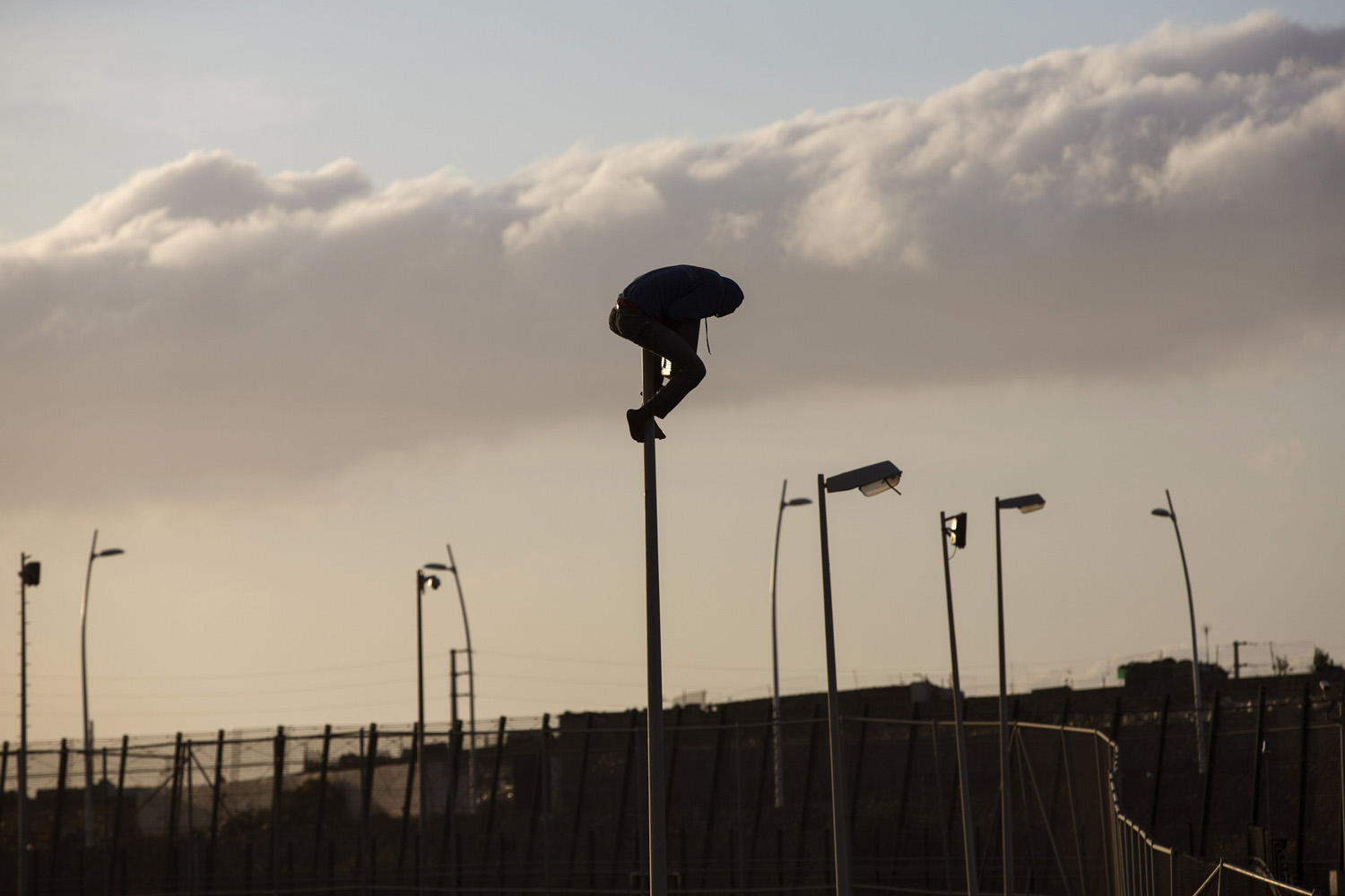 May 28,  2014. A sub-Saharan migrant sits on top of a pole set in a metallic fence that divides Morocco and the Spanish enclave of Melilla.