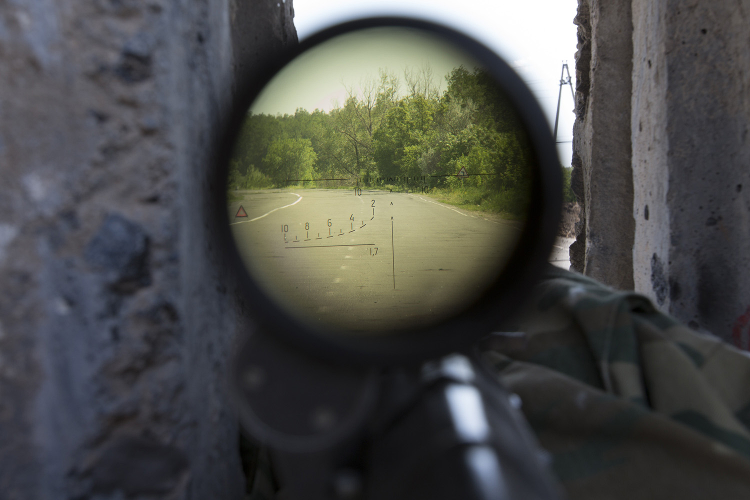 May 18, 2014. A view through a sniper's rifle from a pro-Russian checkpoint blocking the major highway which links Kharkiv, outside  Slovyansk, eastern Ukraine.
