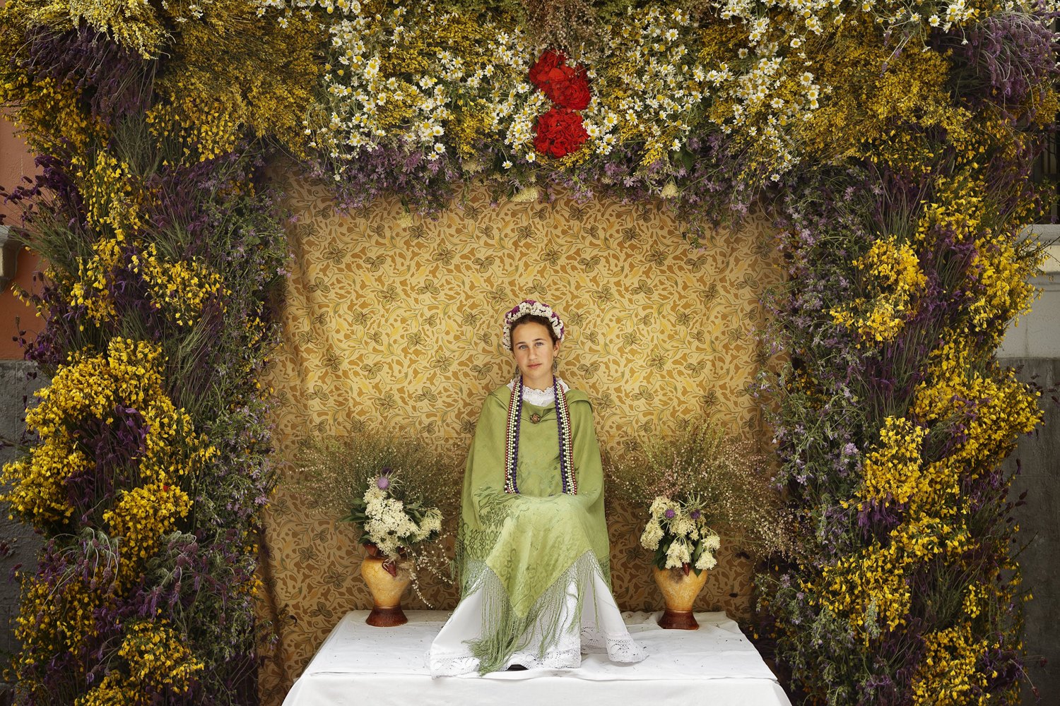 May 11, 2014. A 'Maya' girl sits on an altar during the traditional celebration of 'Las Mayas' on a street, in central Madrid, Spain.