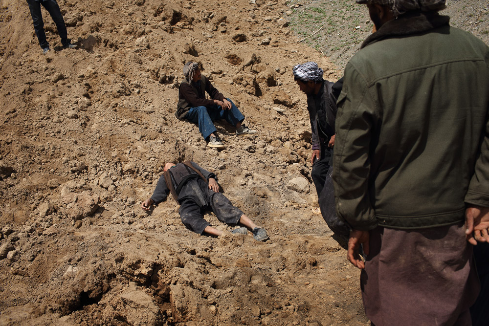 A young boy whose father was killed in the landslide faints as others dig above where his house lies buried, May 5, 2014.
