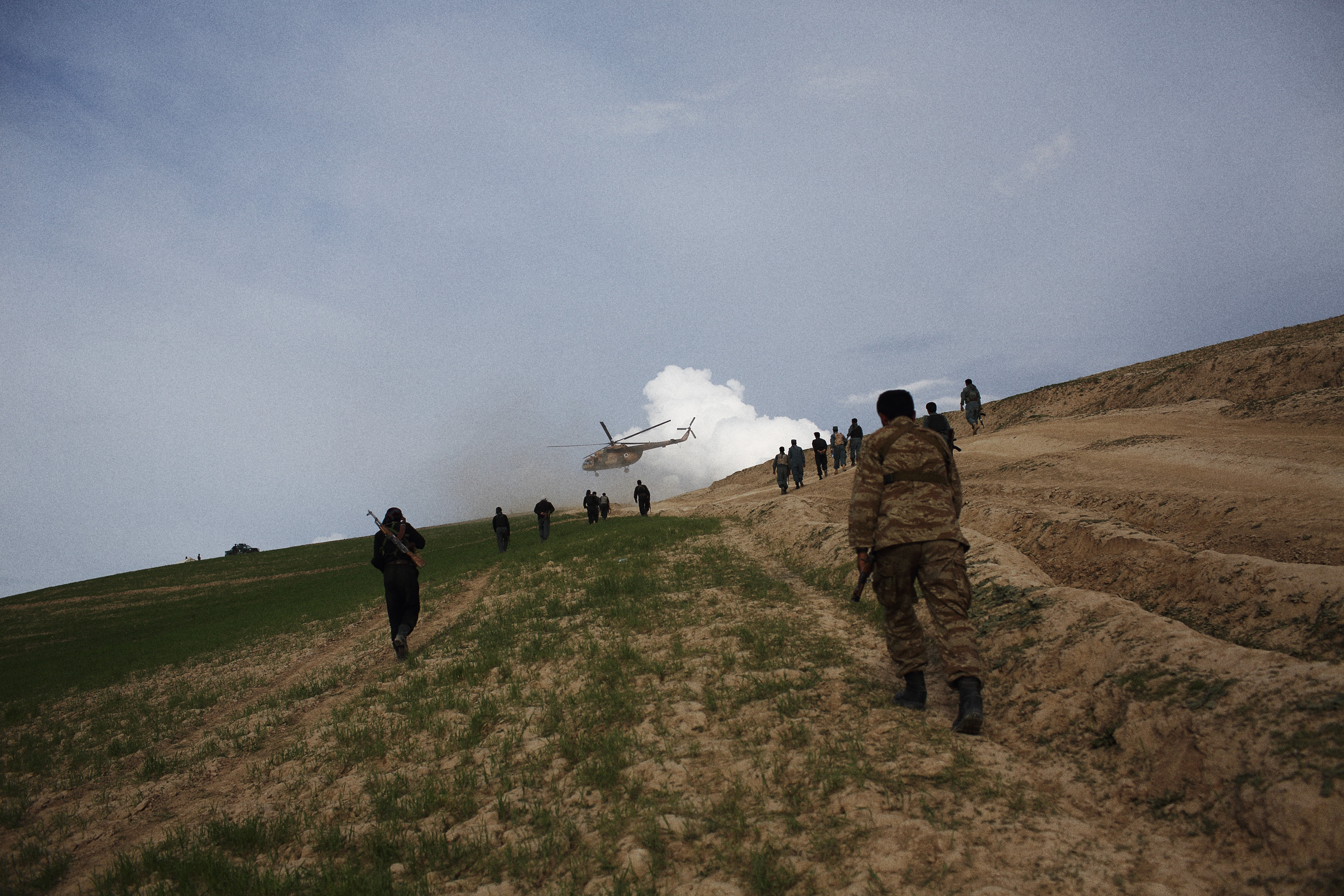 Police climb a hill to guard a helicopter aid delivery, May 6, 2014.