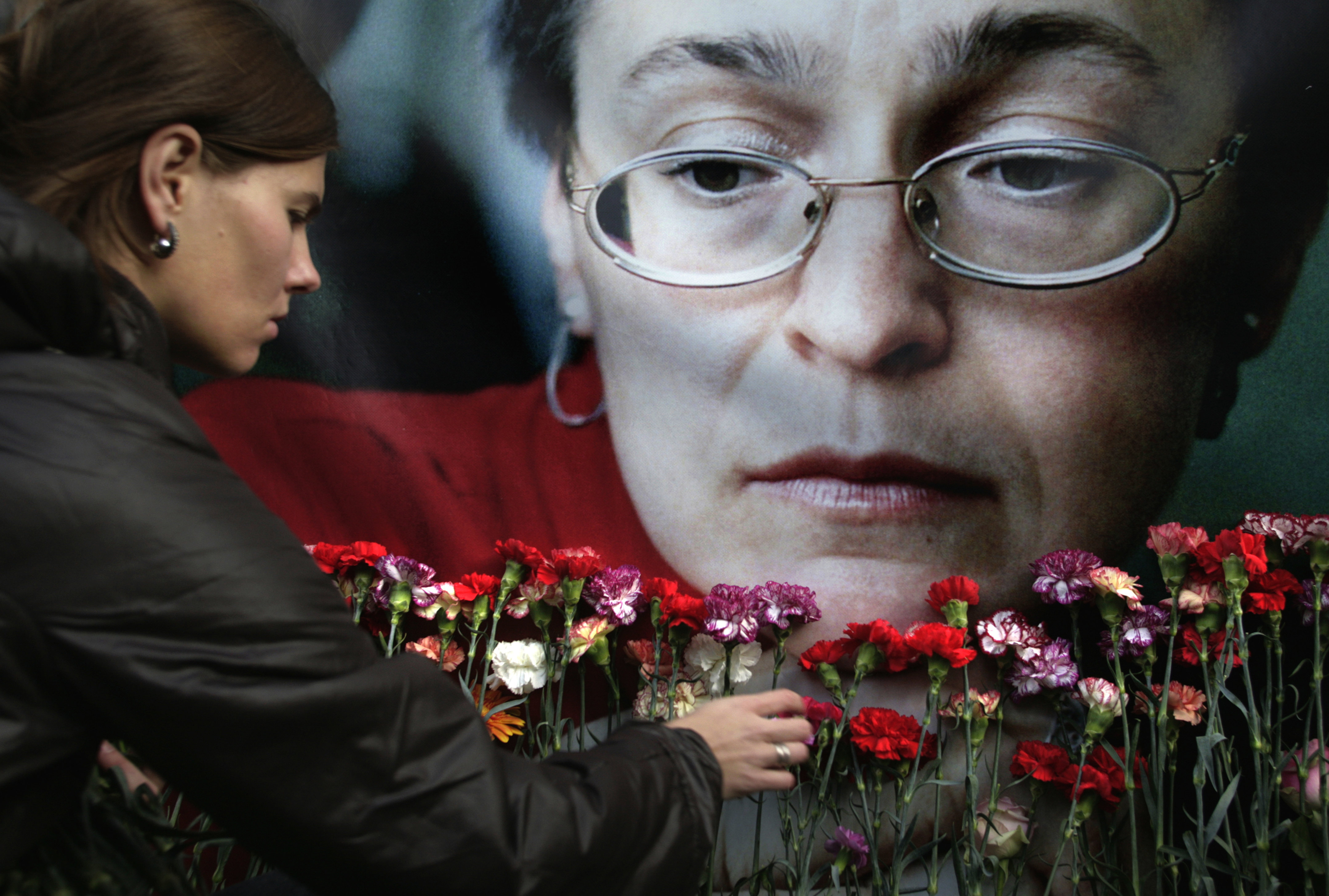 A woman places flowers at a portrait of slain journalist Anna Politkovskaya, during a rally in downtown Moscow, in 2009.