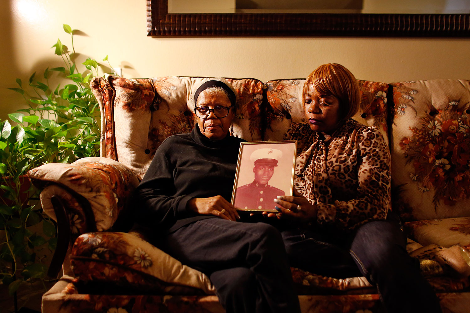 Alma Murdough and her daughter Cheryl Warner hold a photo of Murdough's son, Jerome Murdough, at her home in the Queens borough of New York, March 12, 2014.