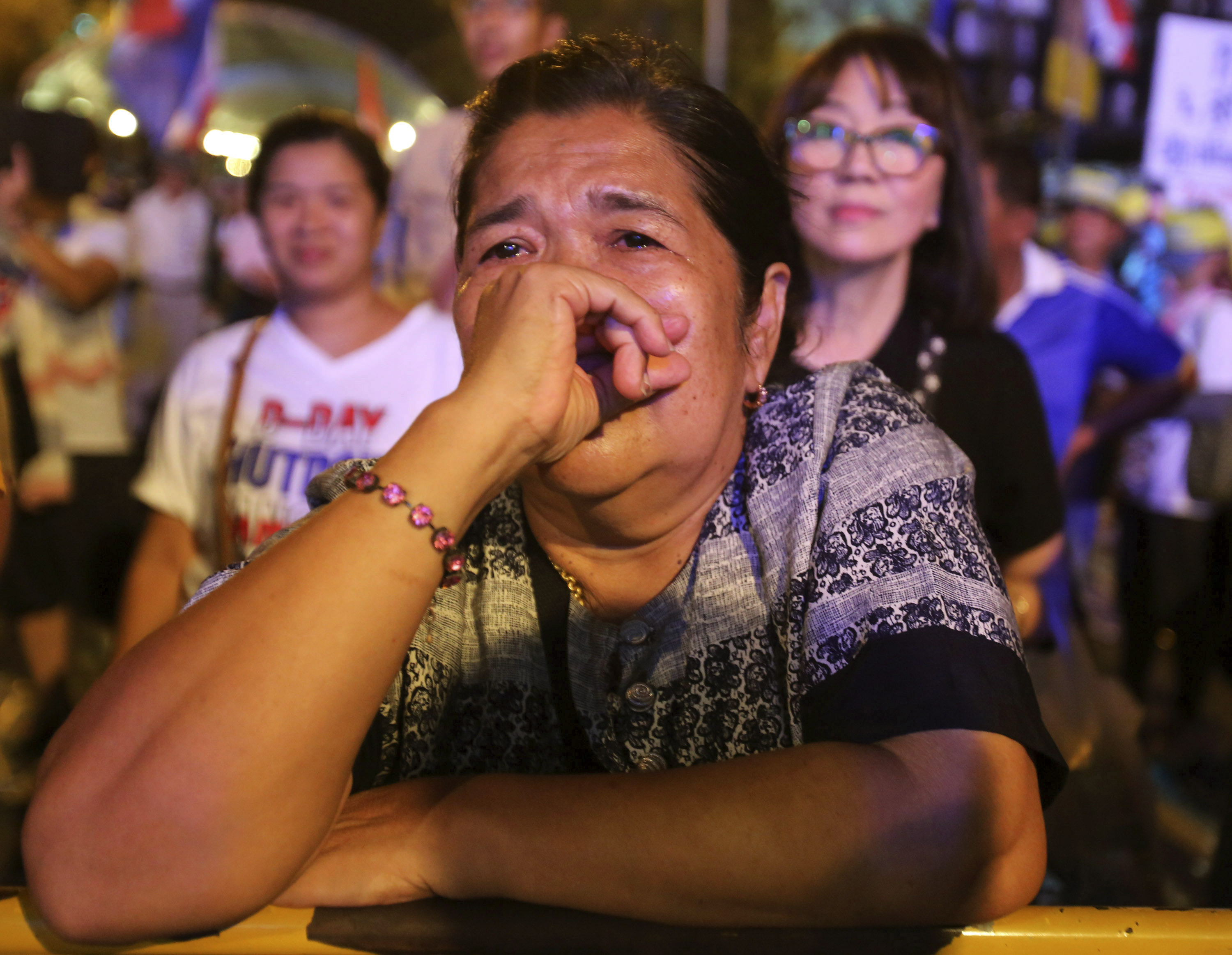An antigovernment demonstrator cries before she leaves a protest site after soldiers staged a coup in Bangkok on Thursday, May 22, 2014.