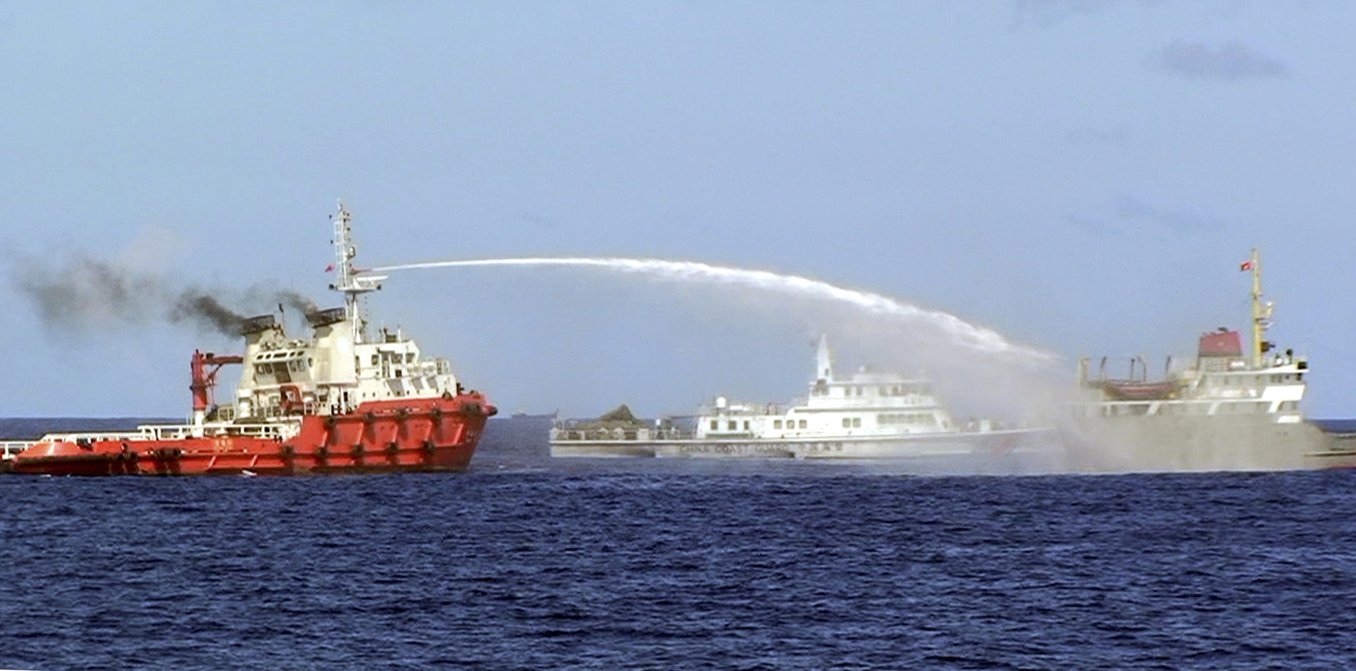 In this photo, released by the Vietnamese Coast Guard, a Chinese ship, left, shoots water cannon at a Vietnamese vessel, right, while a Chinese Coast Guard ship, center, sails alongside in the South China Sea off Vietnam's coast, Wednesday, May 7, 2014. Chinese ships rammed and sprayed water cannon at Vietnamese vessels trying to stop Beijing from setting up an oil rig in the area, according to Vietnamese officials and video evidence.