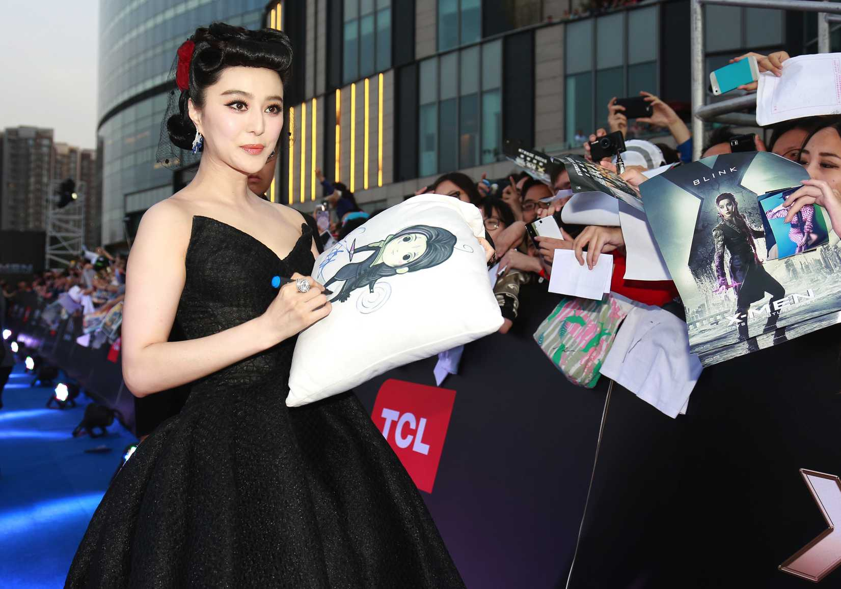 Chinese actress Fan Bingbing signs autographs for fans as she arrives at the premiere for her new movie, X-Men: Days of Future Past, in Beijing, China, 13 May 2014.