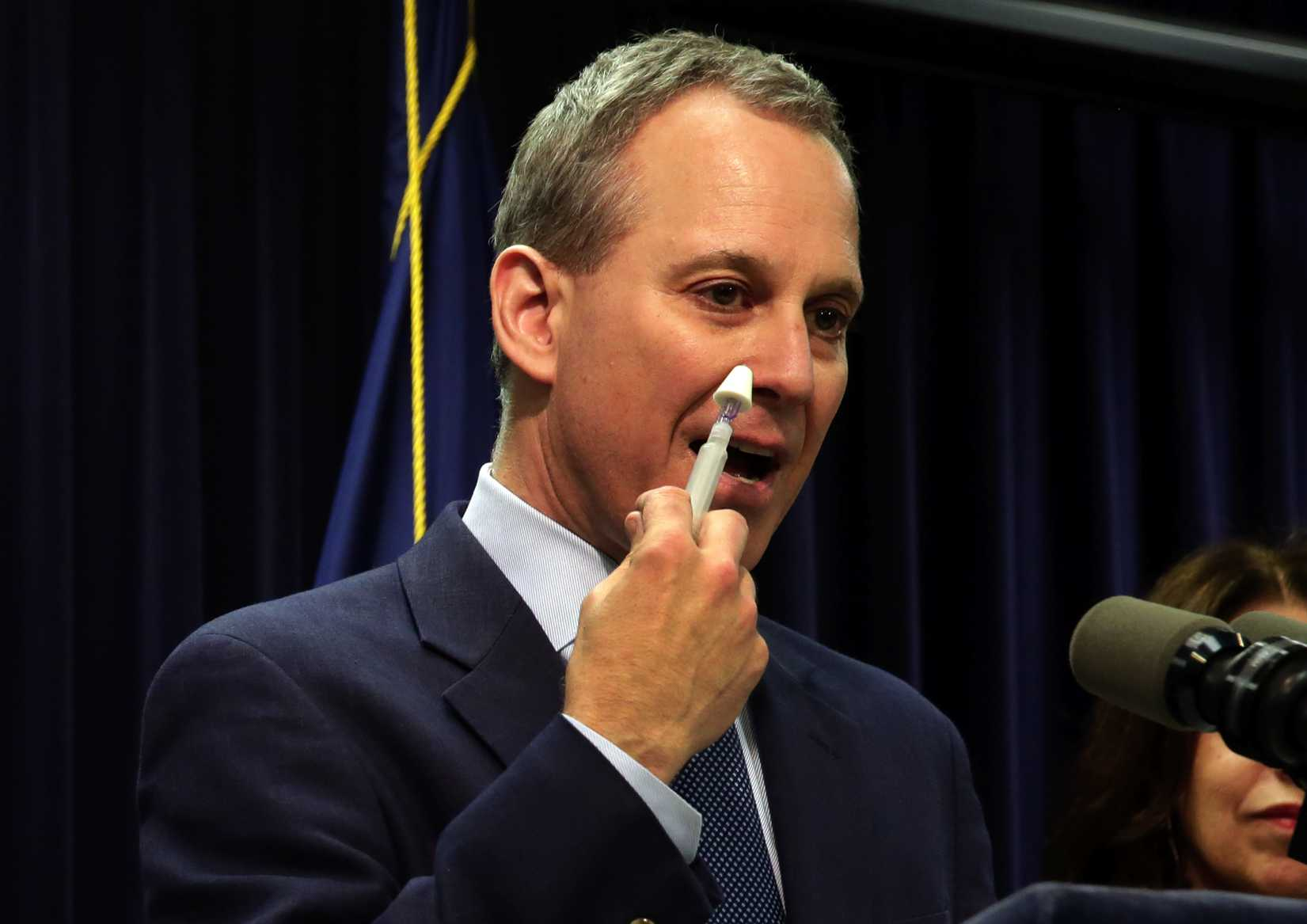New York State Attorney General Eric Schneiderman demonstrates an inhaler of naloxone, a drug to be included in an overdose-prevention rescue kit, during a news conference in New York City on May 27, 2014